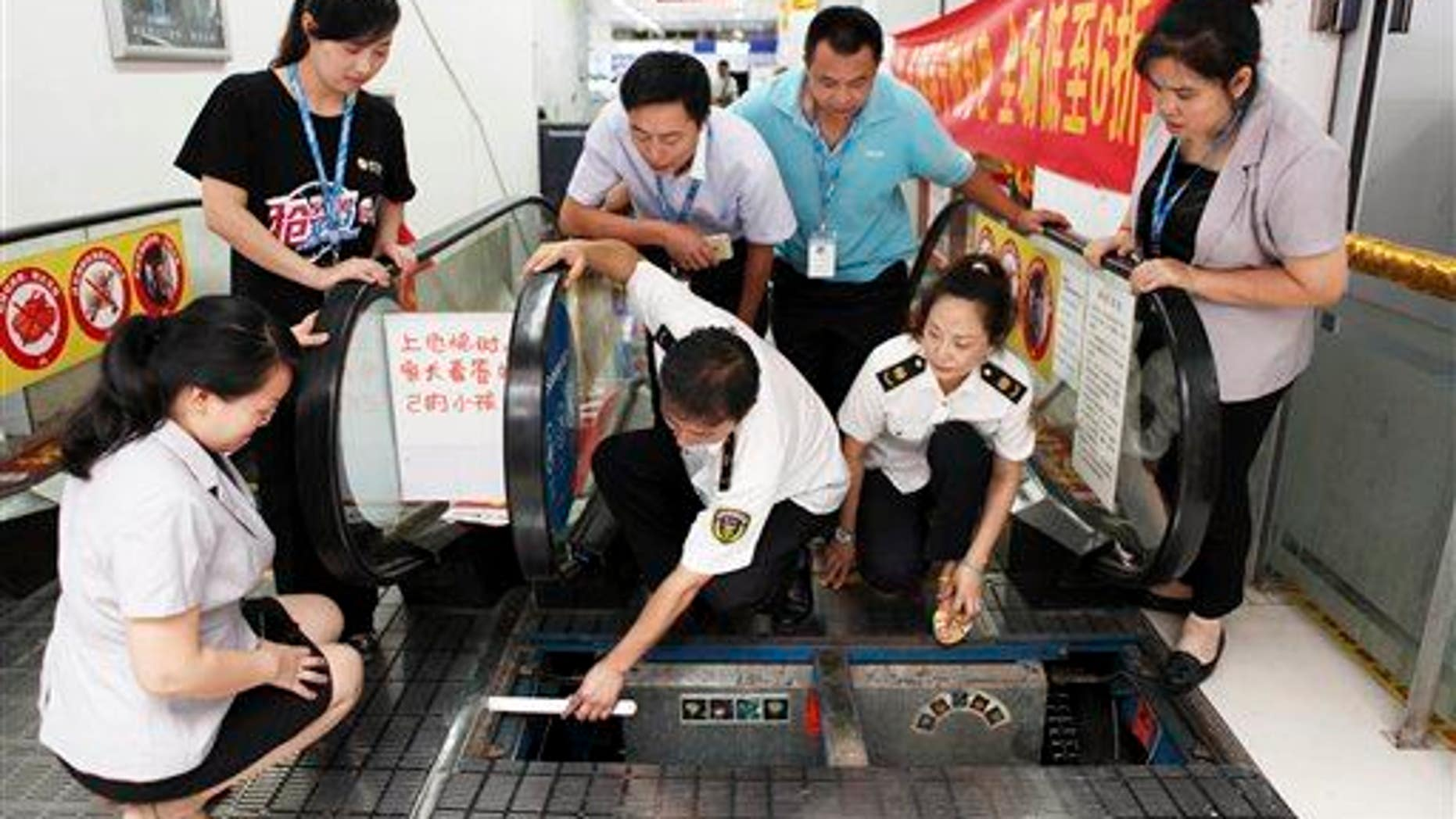 Staff members at an appliance store watch as officials from the local bureau of Quality and Technical Supervision inspect an escalator in Yongchuan district in Chongqing Municipality, July 30, 2015.