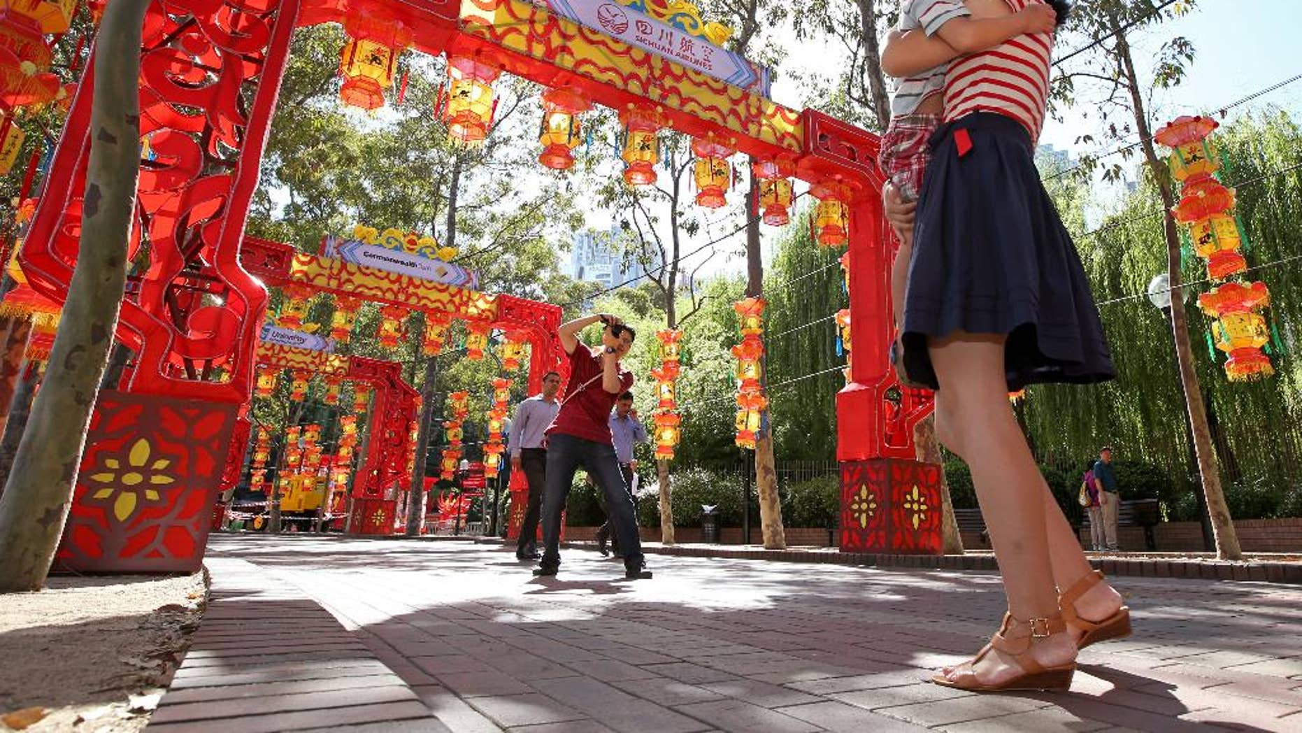 """In this photo taken on Wednesday, Feb. 18, 2015, Pen Pu, center, photographs his wife Chelsea Peng, right, and their three-year-old son Dore Peng, amongst a colorful display of arches and lanterns near the Chinese Garden of Friendship in Sydney, Australia. The gardens, conceived by Chinese landscape artists in consultation with the local Chinese community, are a popular destination for tourists and residents and is located next to the Chinatown district in Sydney.  Pu, 35, who is Chinese but a permanent resident of Australia, says that for the coming New Year he has hopes that """"our country will be peaceful and will get stronger and my family will be happy and healthy."""" (AP Photo/Rick Rycroft)"""