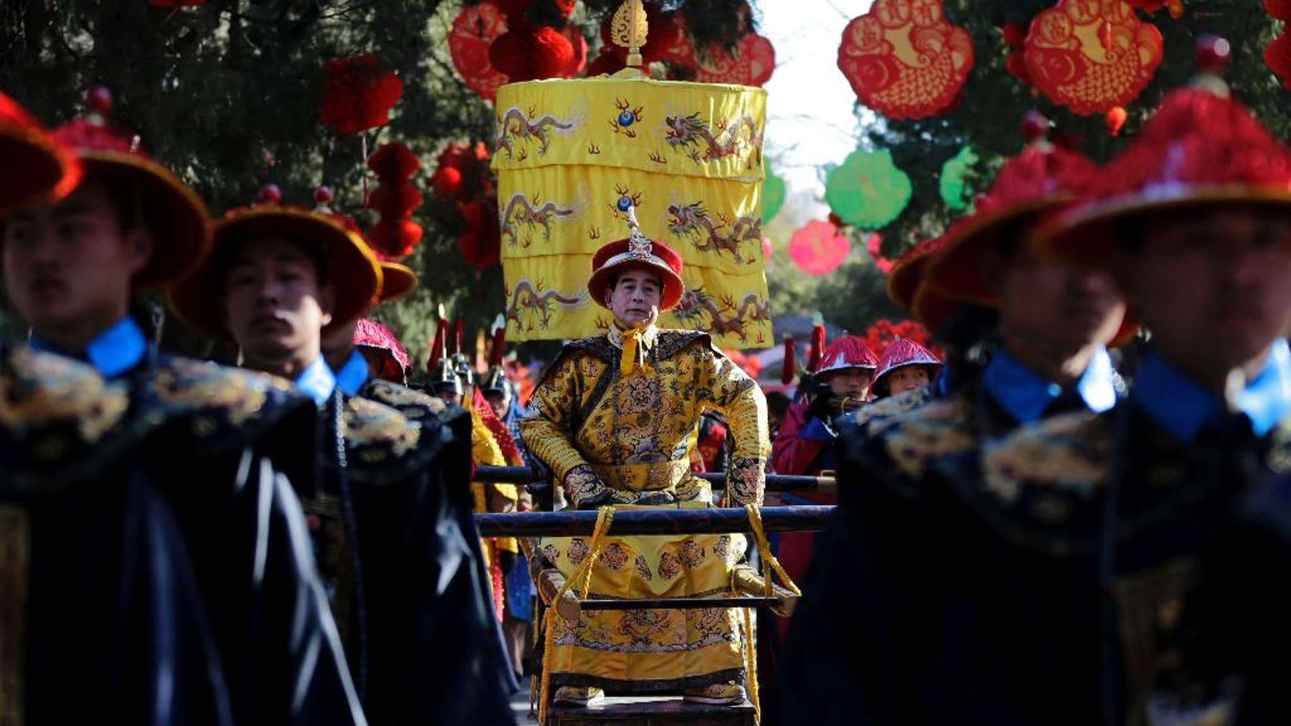 """In this photo taken Wednesday, Feb. 18, 2015, Qi Xue'en, a performer dressed as a Qing Dynasty emperor, seated at center, is carried during a re-enactment of an ancient sacrificial ceremony at Beijing's Ditan Park, the """"Altar of the Earth,"""" on the eve of the Lunar New Year. Ditan Park is one of four altars dedicated to worship of the natural elements under the principles of Chinese cosmology and geomancy, popularly known as feng shui. During the seven-day Lunar New Year holiday, the parks throng with visitors shopping for festive goods, joining in carnival games and taking a break from hectic modern life. """"I have been playing the part of emperor since 1990. I have two apprentices and several pupils now,"""" Qi, 58, said. """"Today and tomorrow, I will play the part of emperor, so I can send New Year's greetings to people I know. Let the pupils play on the second and third days of the Lunar New Year. I am getting old."""" (AP Photo/Andy Wong)"""