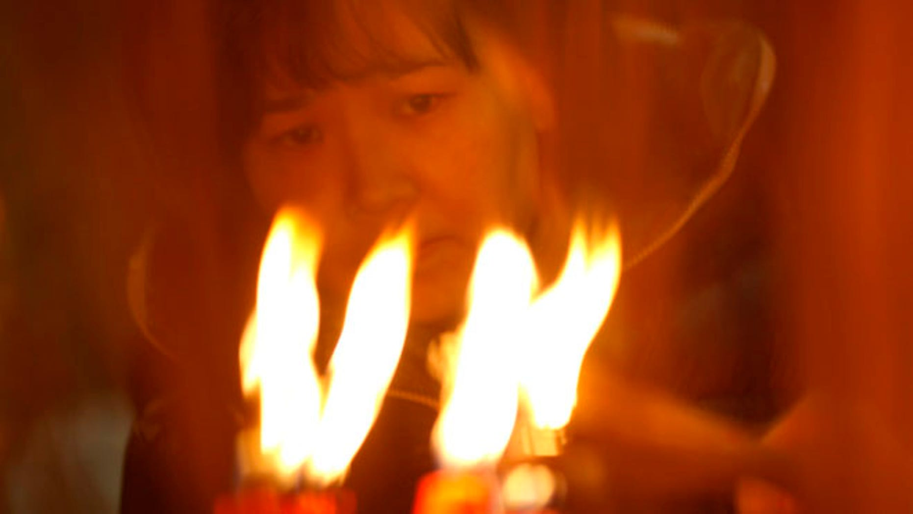 A worshipper burns joss sticks at a temple on the third day of the Chinese Lunar New Year celebrations Wednesday Jan. 25, 2012 in Hong Kong. (AP Photo/Vincent Yu)