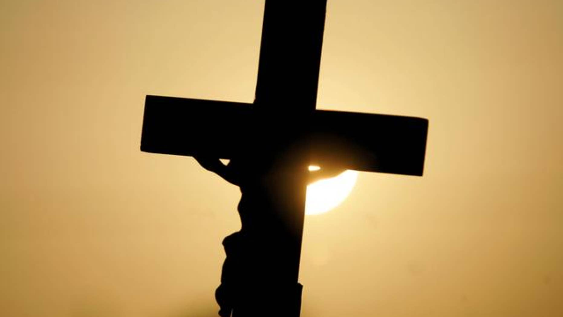 FILE -- A cross is silhouetted against the sun outside the Woodside Hospice in Pinellas Park, Fla.