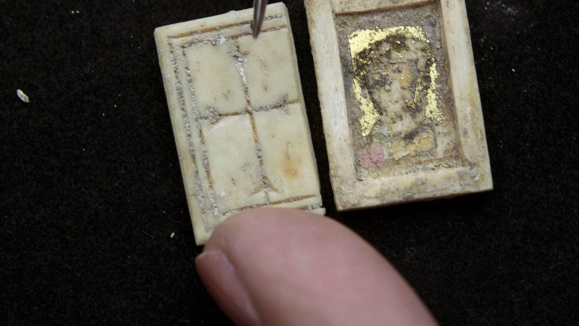 Un restaurador de la Autoridad de Antigüedades de Israel muestra una diinuta caja cristiana bizantina hecha de hueso, con una cruz labrada en la tapa, en Jerusalén, el domingo, 30 de octubre del 2011. El objeto muy probablemete era llevado por un creyente que lo perdiò en una de las calles de la ciudad alrededor del siglo VI, dijeron arqueólogos.(Foto AP/Sebastian Scheiner)