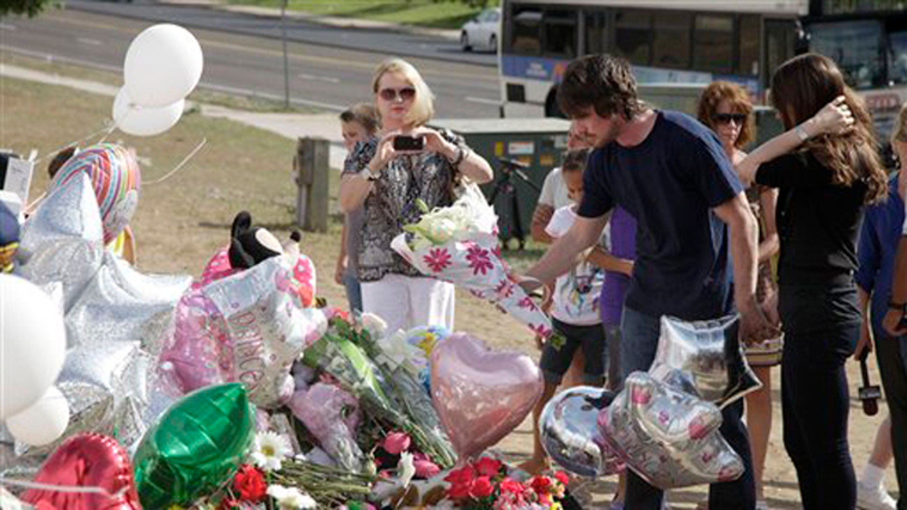 July 24, 2012: Actor Christian Bale, second right, and his wife Sibi Blazic, right, place flowers on a memorial to the victims of Friday's mass shooting in Aurora, Colo.