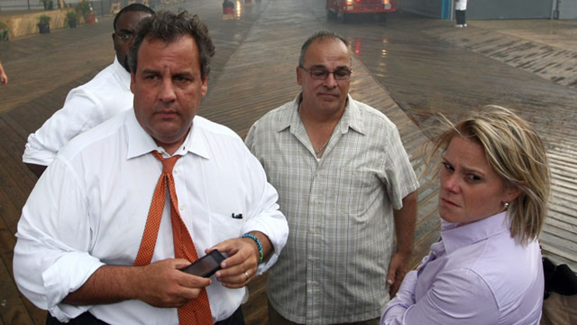 """September 12, 2013: Deputy Chief of Staff Bridget Anne Kelly, right, stands with Gov. Chris Christie, left, during a tour of the Seaside Heights, N.J. boardwalk after it was hit by a massive fire. Christie fired Kelly Thursday, Jan. 9, 2014, and apologized over and over for his staff's """"stupid"""" behavior, insisting during a nearly two-hour news conference that he had no idea anyone around him had engineered traffic jams as part of a political vendetta against a Democratic mayor. (AP Photo/Office of Gov. Chris Christie, Tim Larsen)"""