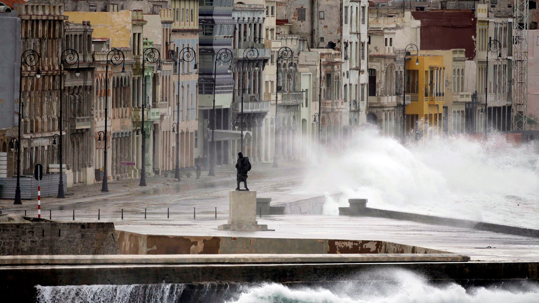 FILE - In this Dec. 13, 2010 file photo, a statue of Venezuelan independence hero Francisco de Miranda stands as waves splash over the sea wall onto Malecon Avenue during heavy winds in Havana, Cuba. Thousands of Cuban-Americans are heading to Havana this holiday season carrying everything from electronics and medicine to clothing and toiletries to help relatives back home supplement monthly salaries averaging about $20. Not only are Cuban-Americans visiting the island in far greater numbers since President Barack Obama lifted travel restrictions last year, they are bringing more stuff. One carrier says the average bag weight per passenger is up 55 percent _ and many Miami-Havana flights are shadowed by a separate cargo plane just to haul the load. (AP Photo/Javier Galeano, File)