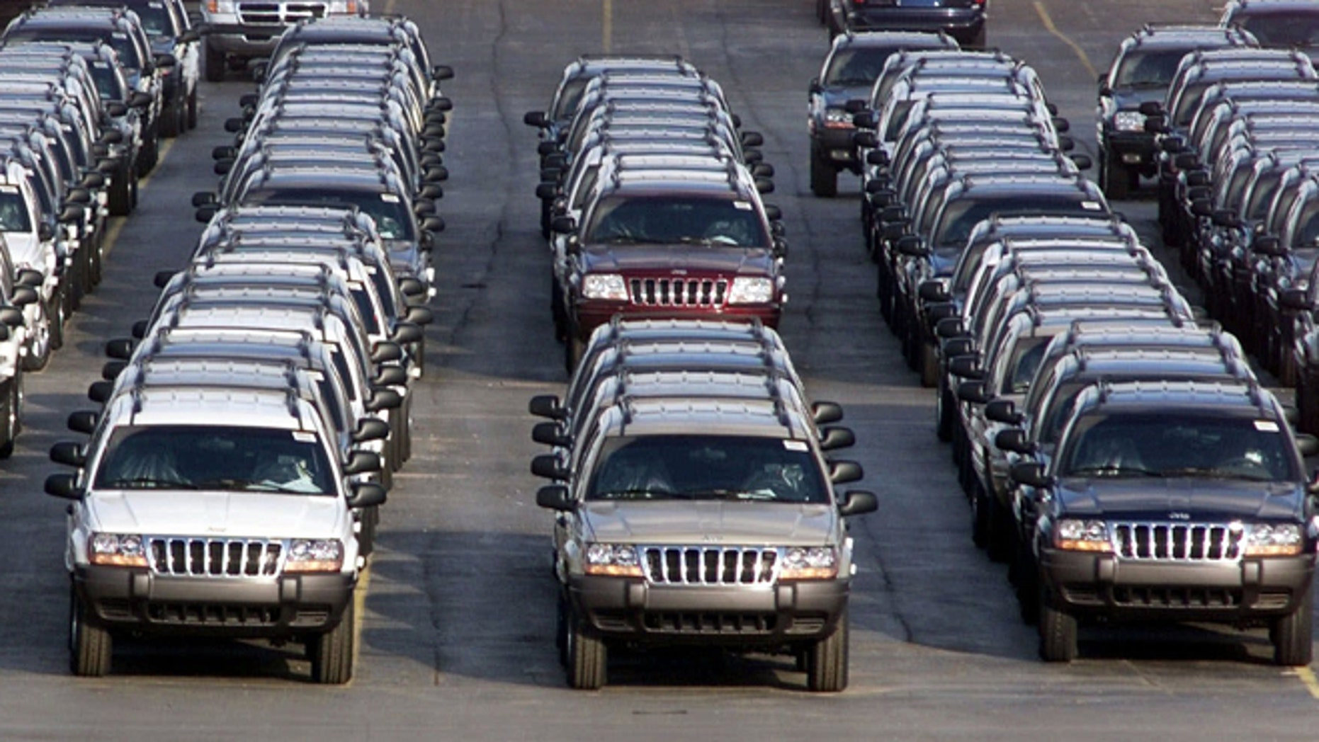 FILE - In this file photo taken Fed. 2, 2001, rows of 2001 Jeep Grand Cherokees are lined up outside the Jefferson North Assembly Plant in Detroit.  (AP Photo/Carlos Osorio, File)