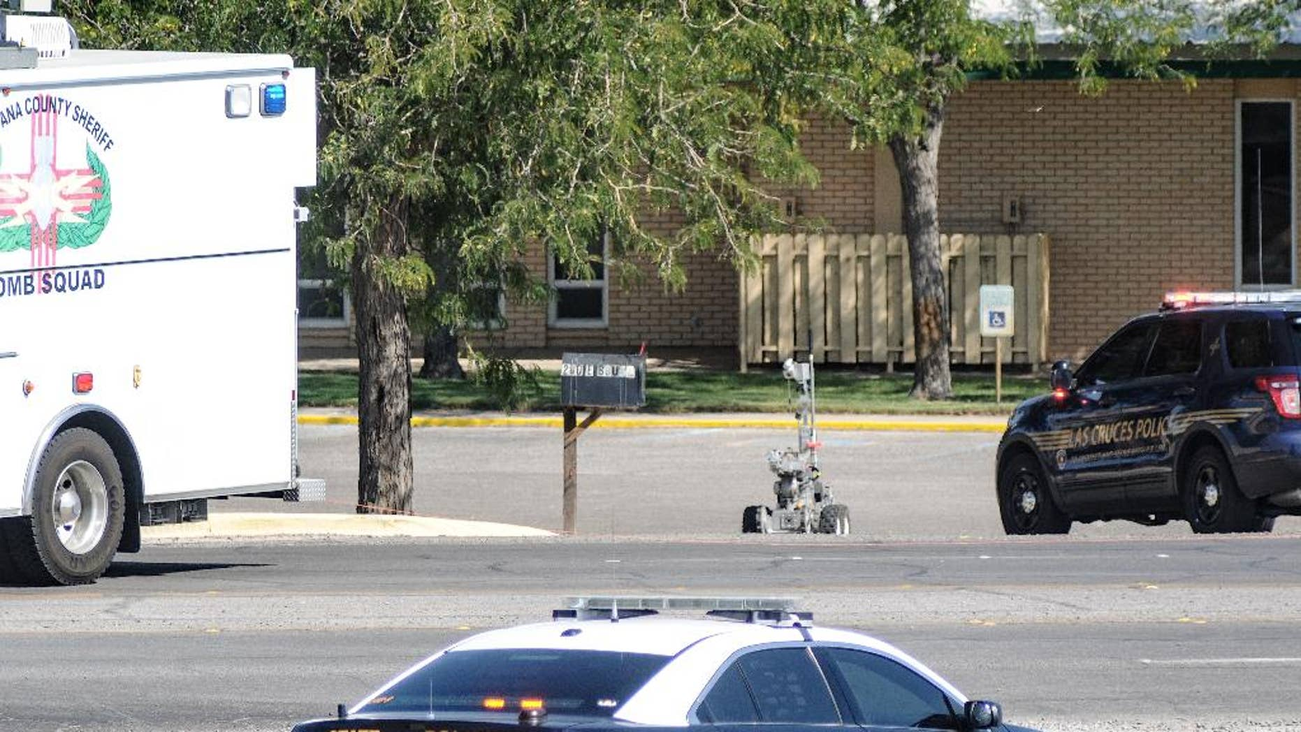 A Dona Ana County bomb squad robot is deployed to examine a suspicious package at the First Presbyterian Church, Friday, Aug. 14, 2015, in Las Cruces, N.M. The device was found Friday morning by a groundskeeper at the church. Police haven't released any details about the device. The incident comes just weeks after the detonation of explosive devices outside two other Las Cruces churches. (Robin Zielinski/The Las Cruces Sun-News via AP) MANDATORY CREDIT