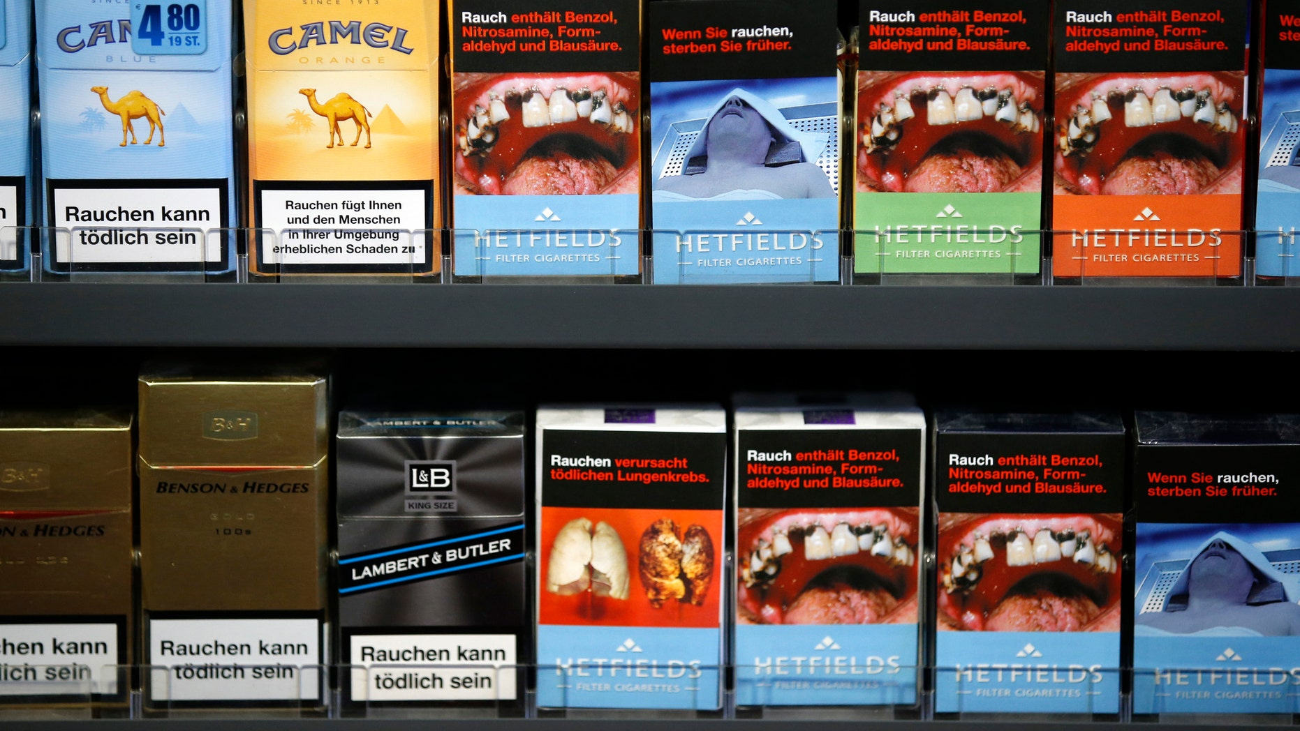 Cigarette boxes with an affixed, self-made cigarette label displaying graphic images and those with the original label are pictured in Berlin February 9, 2013.