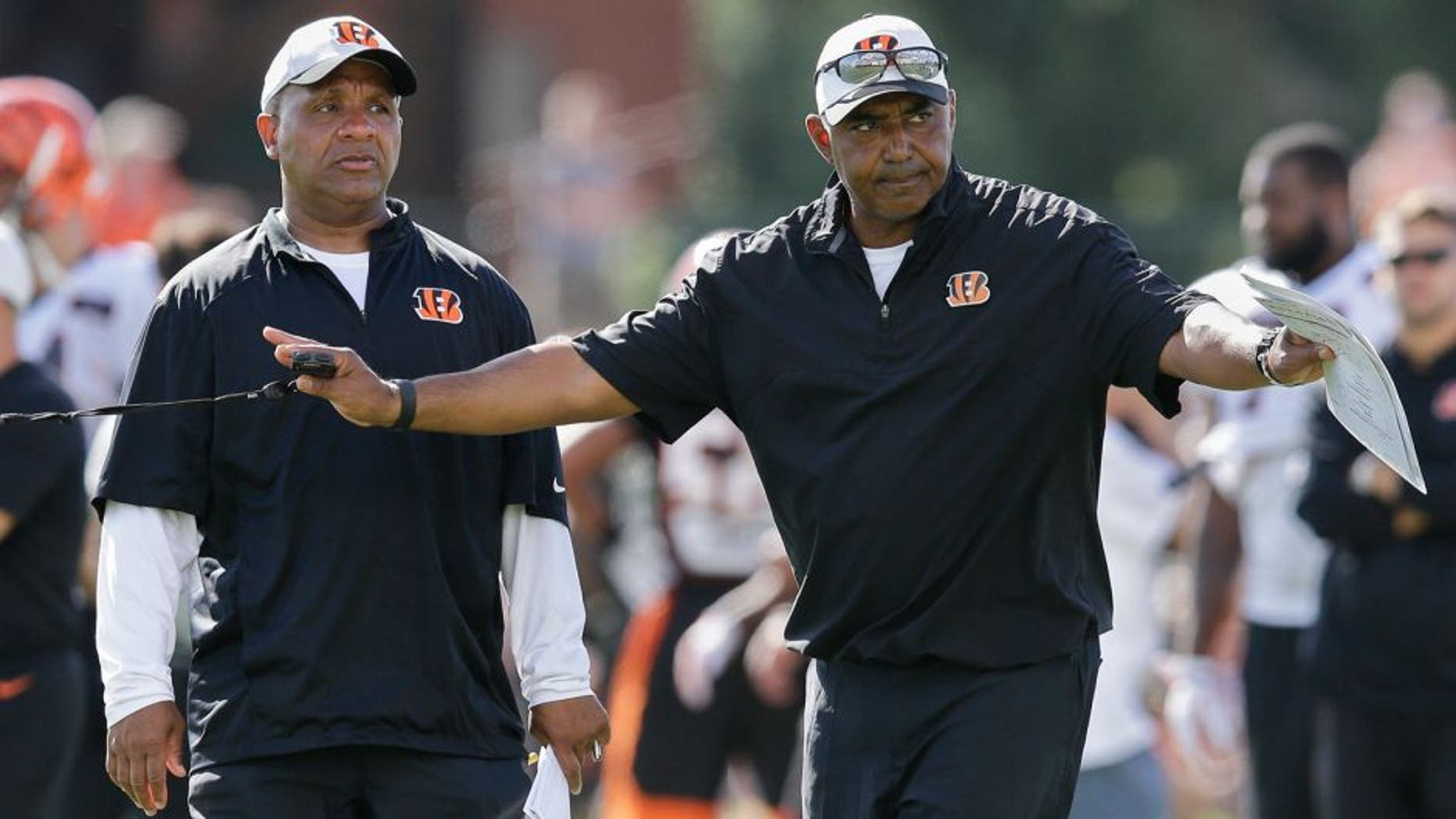 Cincinnati Bengals coach Marvin Lewis, right, signals to his players alongside offensive coordinator Hue Jackson, left, during a joint NFL football training camp with the New York Giants, Wednesday, Aug. 12, 2015, in Cincinnati. (AP Photo/John Minchillo)