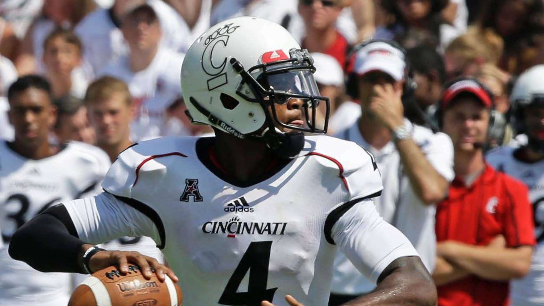 FILE - In this Aug. 31, 2013, file photo, Cincinnati quarterback Munchie Legaux throws a pass in an NCAA college football game in Cincinnati. Legaux received another year of eligibility when he suffered a knee injury in the fall of 2013 and was able to briefly play as a backup in the Bearcats win over Toledo last Friday. (AP Photo/Al Behrman, File)