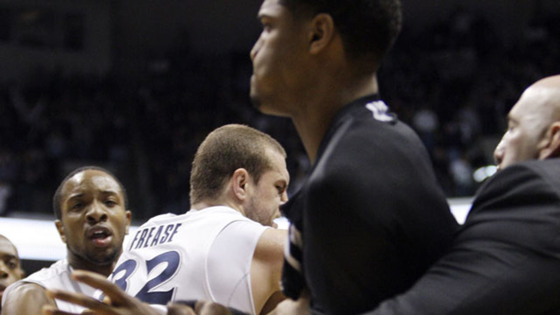 December 10, 2011: Xavier's Dezmine Wells, left, and center Kenny Frease (32) are held back while a Cincinnati coach holds back a player during a fight at the end of an NCAA college basketball game.