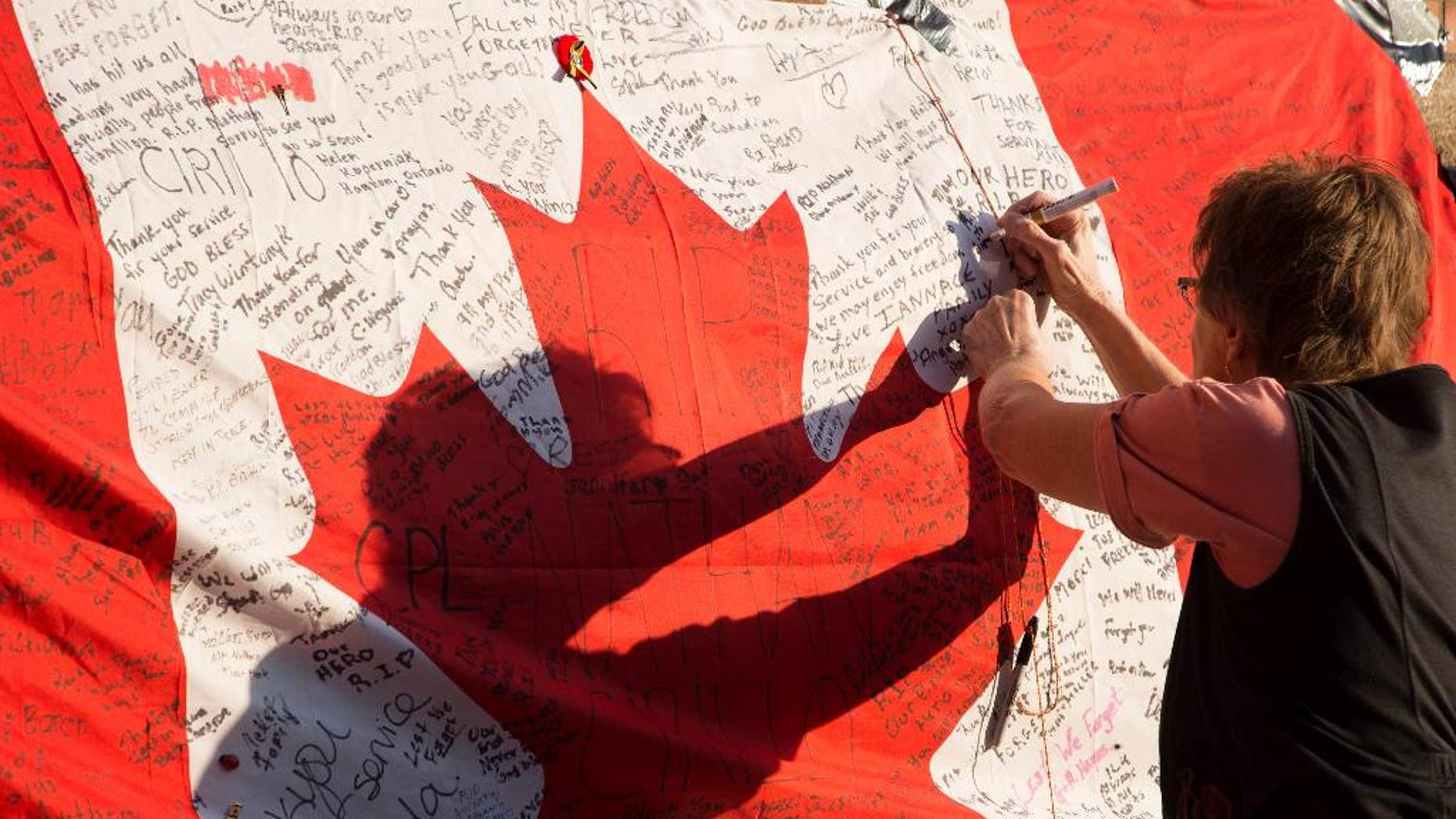 People continue to visit and build upon the memorial to Cpl Nathan Cirillo that has been growing outside of The Lieutenant-Colonel John Weir Foote Armoury in Hamilton, Ontario on Friday, Oct. 24, 2014. Cirillo, a reserve soldier with the Argyll and Sutherland Highlanders, was killed by an armed gunman on Parliament Hill early on Wednesday morning. (AP Photo/The Canadian Press, Peter Power)