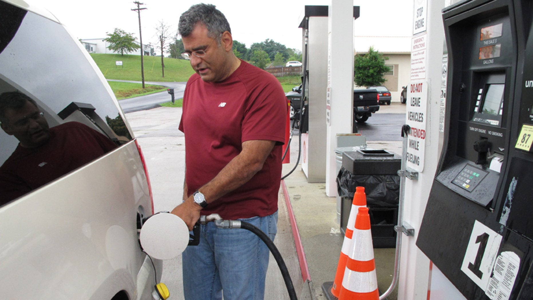 Samir Cook fills up his vehicle at a city-run station on Saturday, July 19, 2014, in Somerset, Ky. The station on the outskirts of Somerset opened to the public on Saturday, selling regular unleaded gas for $3.36 a gallon. In the first three hours, about 75 customers fueled up at the no-frills city station, where there are no snacks, no repairs and only regular unleaded gas. The citys mayor says he hopes the no-frills station will lower gas prices around town. (AP Photo/Bruce Schreiner)