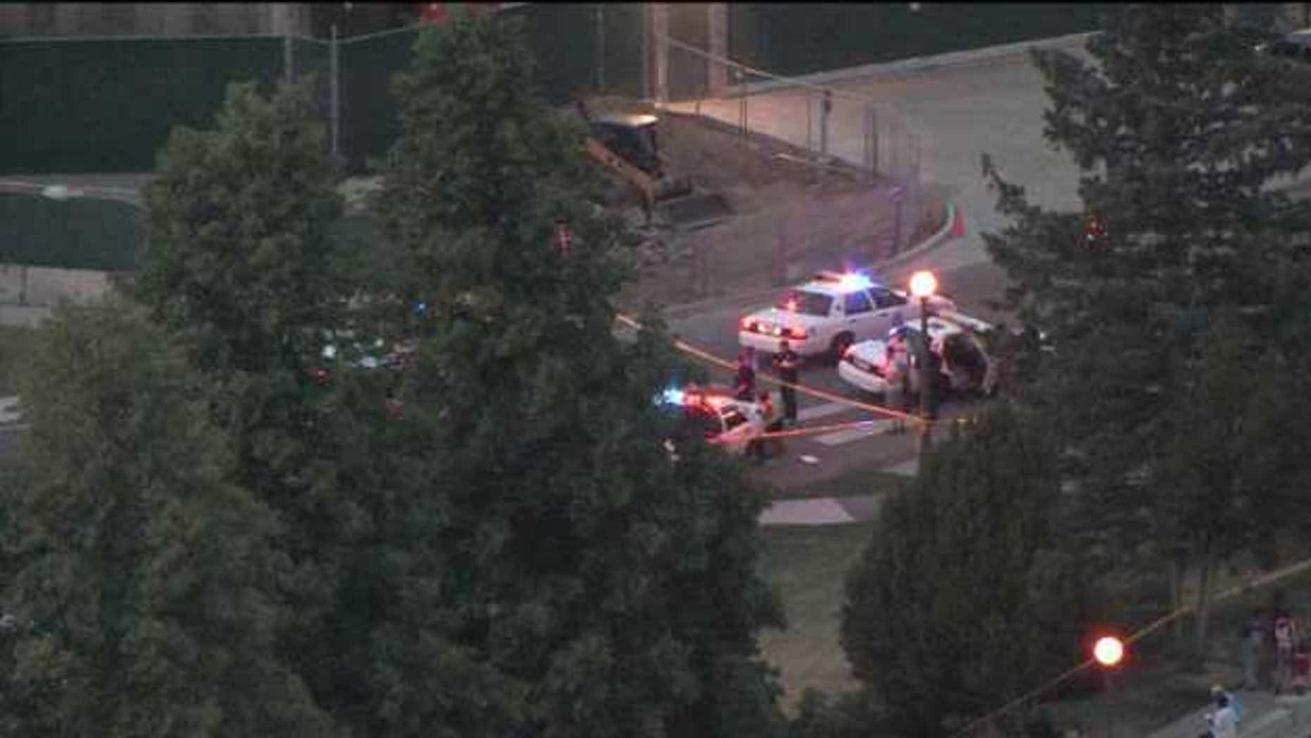 June 24, 2012: Police officers gather at the scene of a shooting at City Park in Denver.