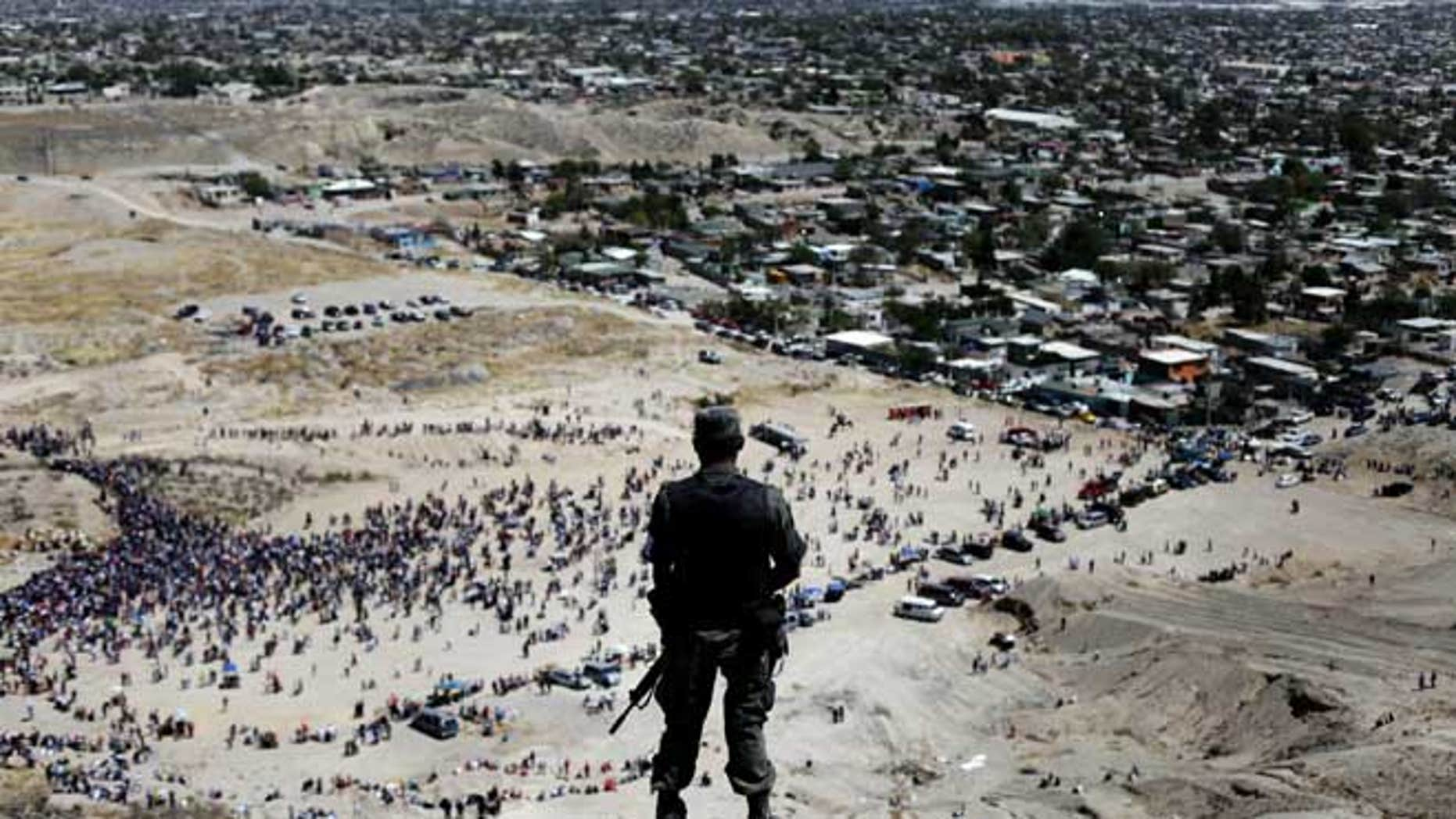 In this April 10, 2009 file photo, a soldier stands guard on the top of a hill as faithful commemorate Good Friday during Holy Week in Ciudad Juarez, Mexico. Killings by criminal gangs in the drug violence-wracked border city of Ciudad Juarez fell by 42 percent in the first six months of this year from the same period of 2011, Mexicoís army said Wednesday July 11, 2012.
