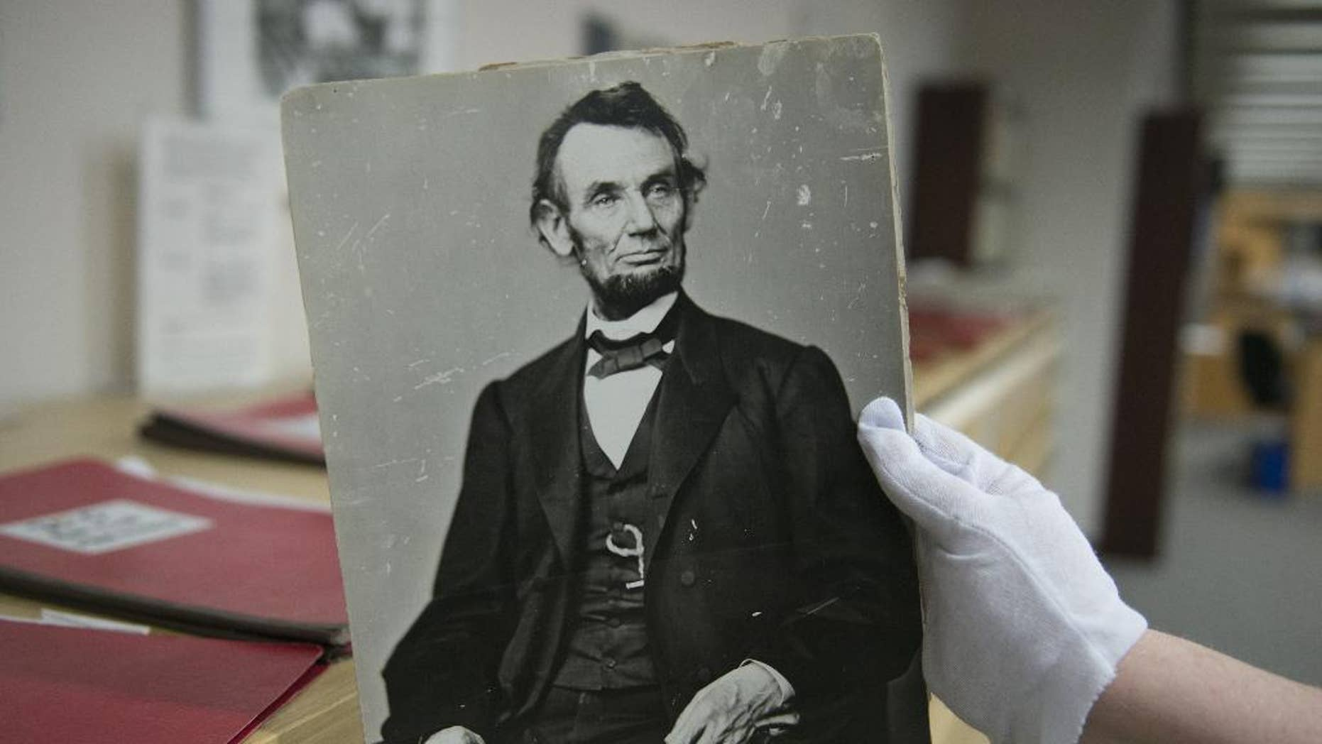 In this Monday, April 6, 2015 photo, Karen Needles holds up a photograph of President Abraham Lincoln at the National Archives in College Park, Md. Three blocks away, 150 years earlier, Lincoln was felled by an assassin's bullet. (AP Photo/Molly Riley)