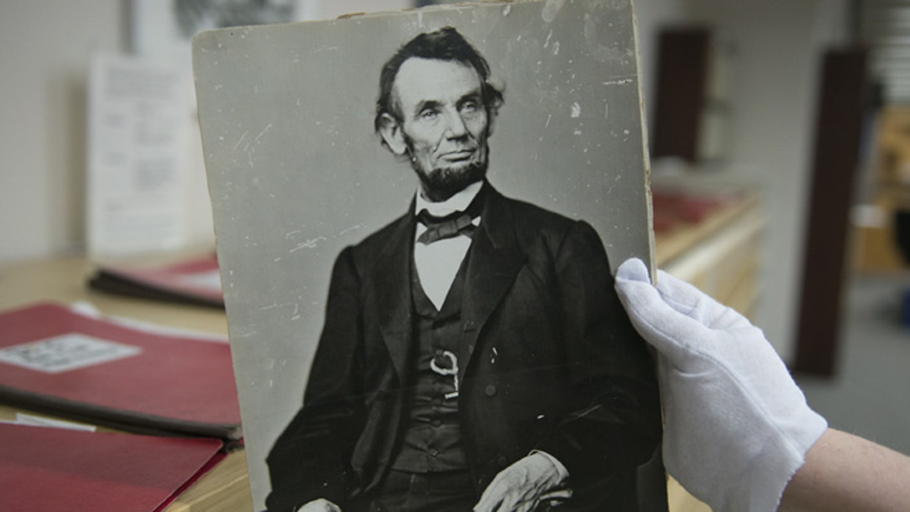 April 6, 2015: Karen Needles holds up a photograph of President Abraham Lincoln at the National Archives in College Park, Md.