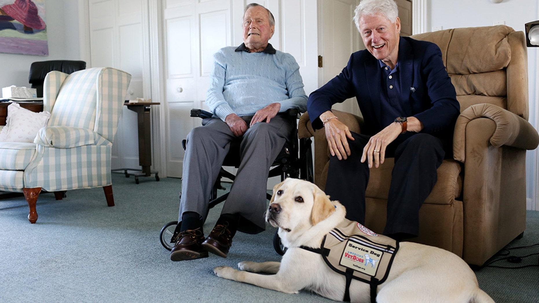 A photo sent via Twitter shows Sully lounging at the feet of Former President George H.W. Bush and former President Bill Clinton, who had been visiting on Monday.