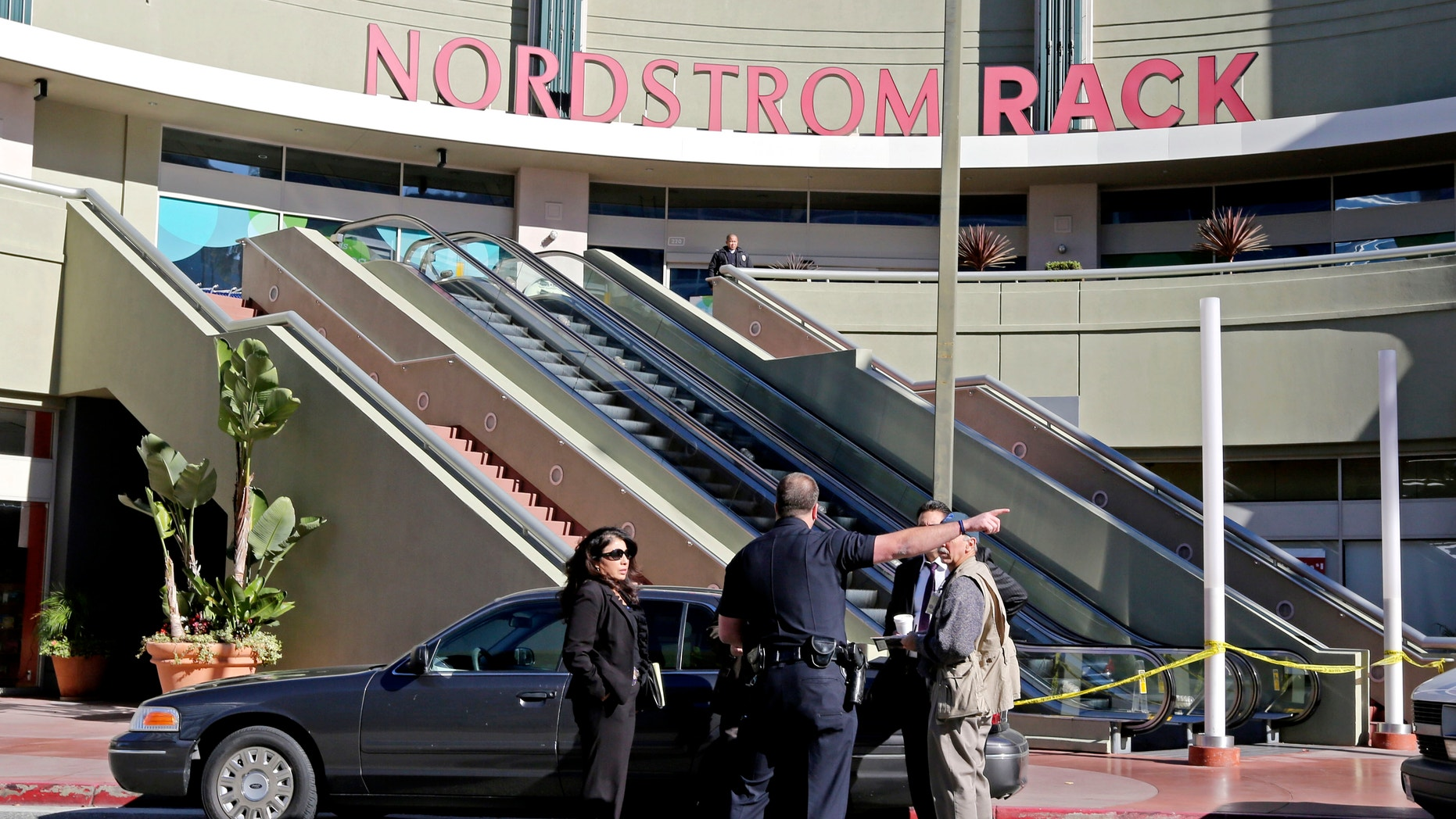 Jan. 11, 2013: Los Angeles police investigators stand outside a Nordstrom Rack store at Howard Hughes Center near Los Angeles International Airport.