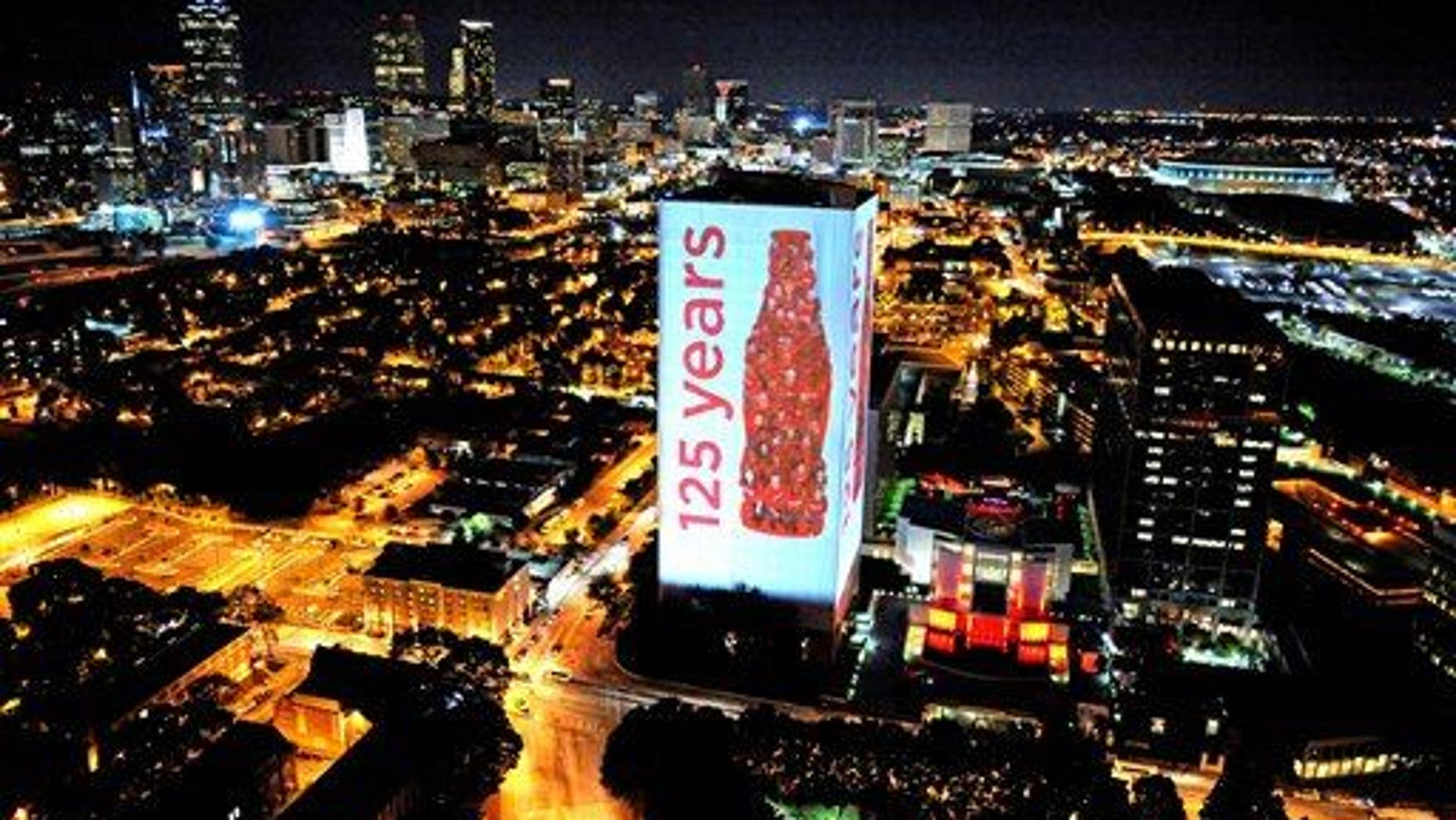 The headquarters building of The Coca-Cola Company is illuminated against the skyline of Atlanta.