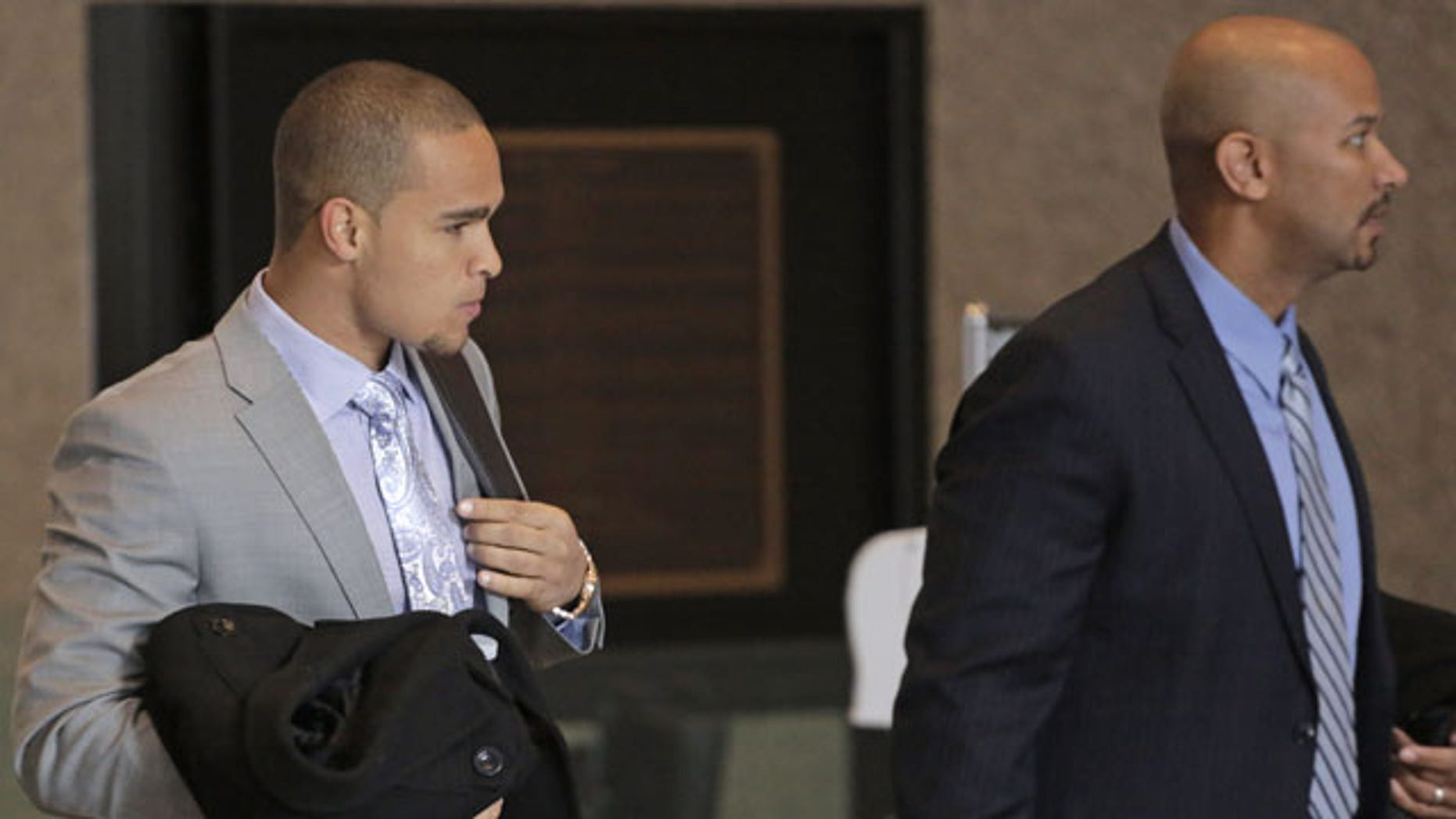 February 18, 2014: College Athletes Players Association designated president Ramogi Huma, right, and Northwestern University Wildcats' outgoing senior quarterback Kain Colter make their way to the beginning of three days of hearings before the National Labor Relations Board in Chicago. (AP)