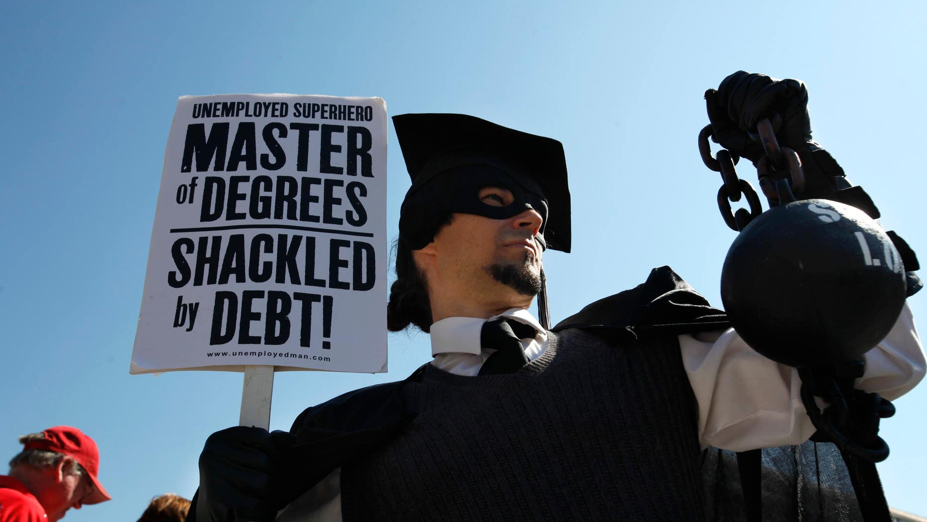 """Oct. 6, 2011: Gan Golan of Los Angeles, dressed as the """"Master of Degrees,"""" holds a ball and chain representing his college loan debt during Occupy DC activities in Washington."""