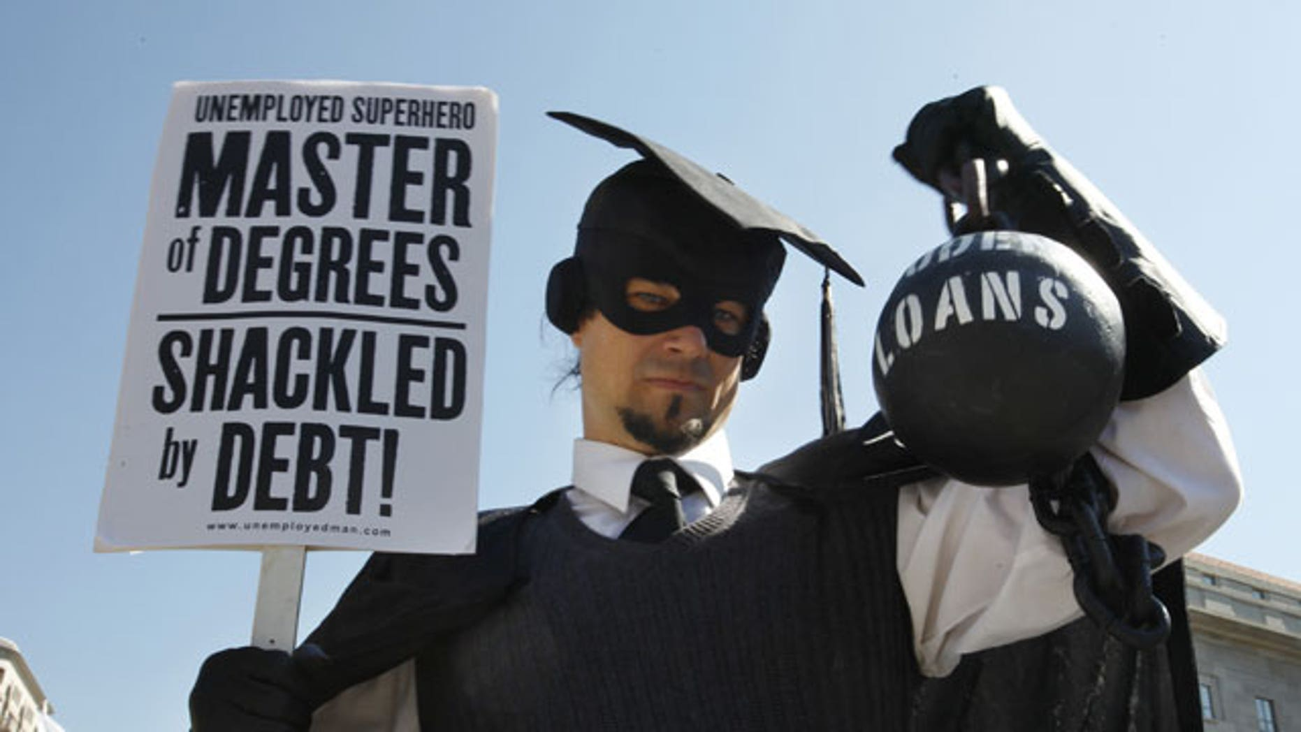 """October 6, 2011:  Gan Golan, of Los Angeles, dressed as the """"Master of Degrees,"""" holds a ball and chain representing his college loan debt, during Occupy DC activities in Washington."""