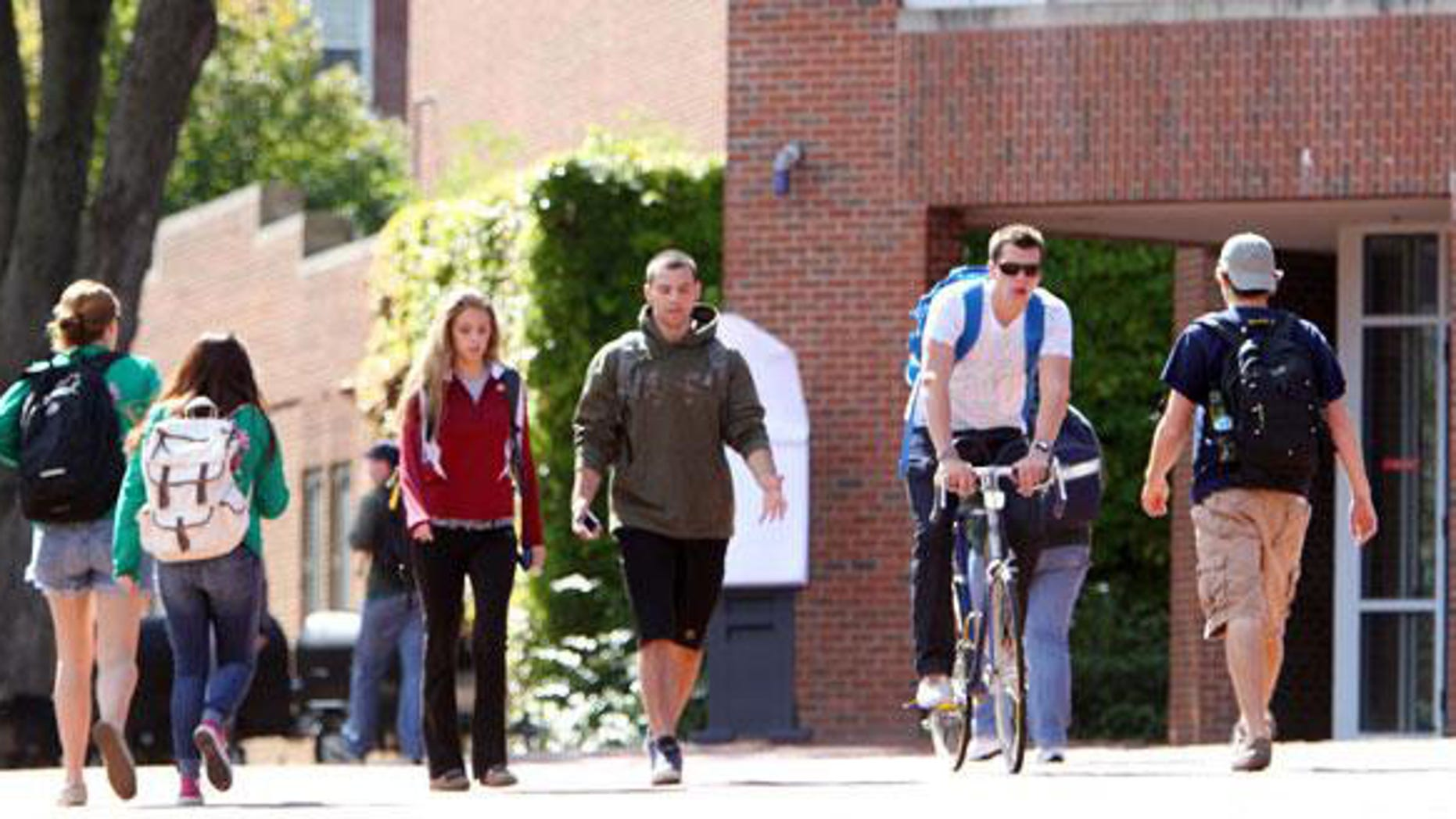 Students are pictured walking through a college campus.