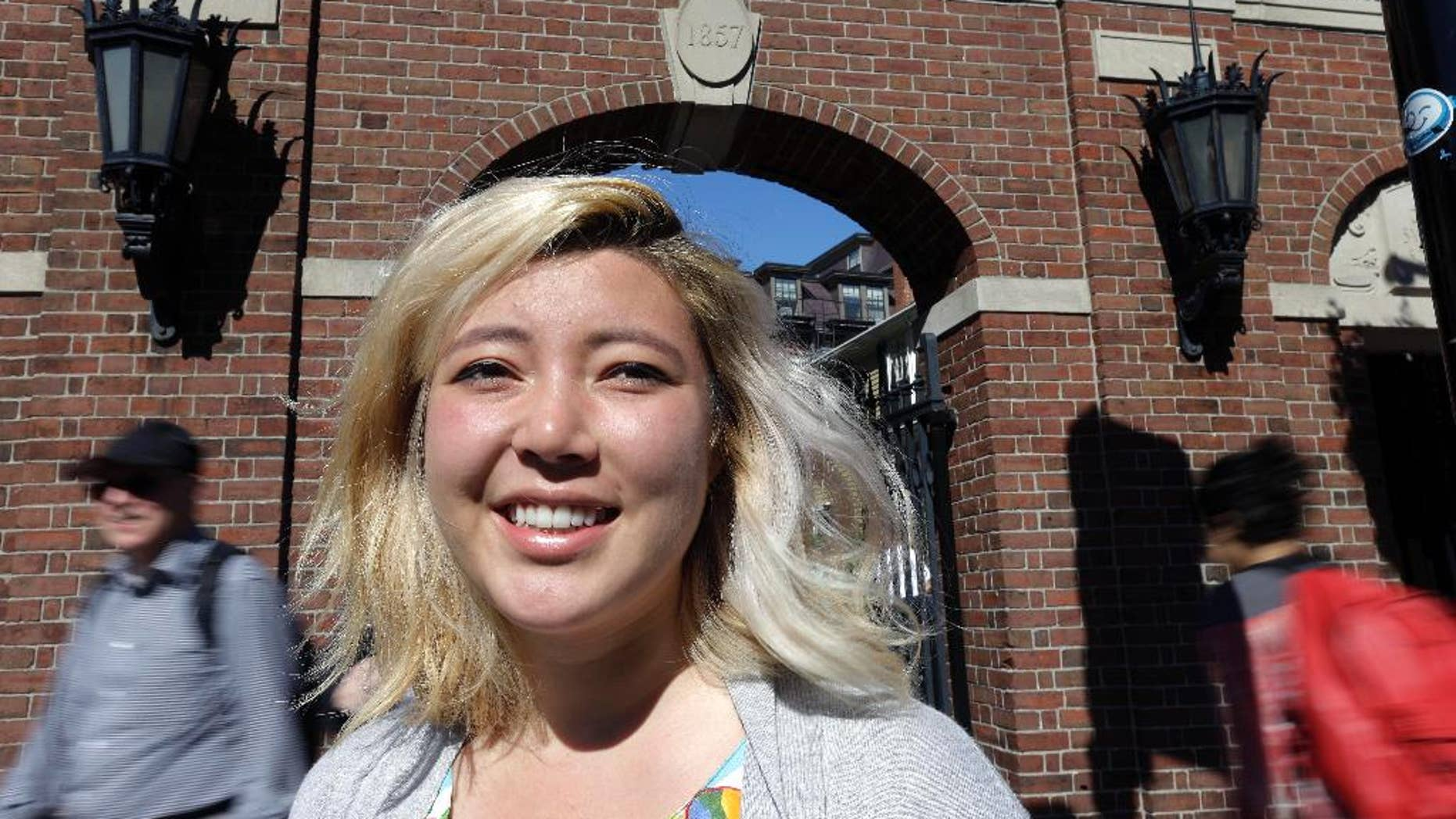 """In this Thursday, Sept. 17, 2015 photo, Laila Smith, a junior at Harvard University, poses at a gate leading to Harvard Yard in Cambridge, Mass. During the registration process, students at Harvard are now allowed to indicate which pronouns they use. Forms include typical options like """"he"""" and """"she"""" but also gender-neutral options like """"ze"""" or """"they."""" Smith filled in the pronouns """"they"""" and """"their"""" on the form. (AP Photo/Steven Senne)"""