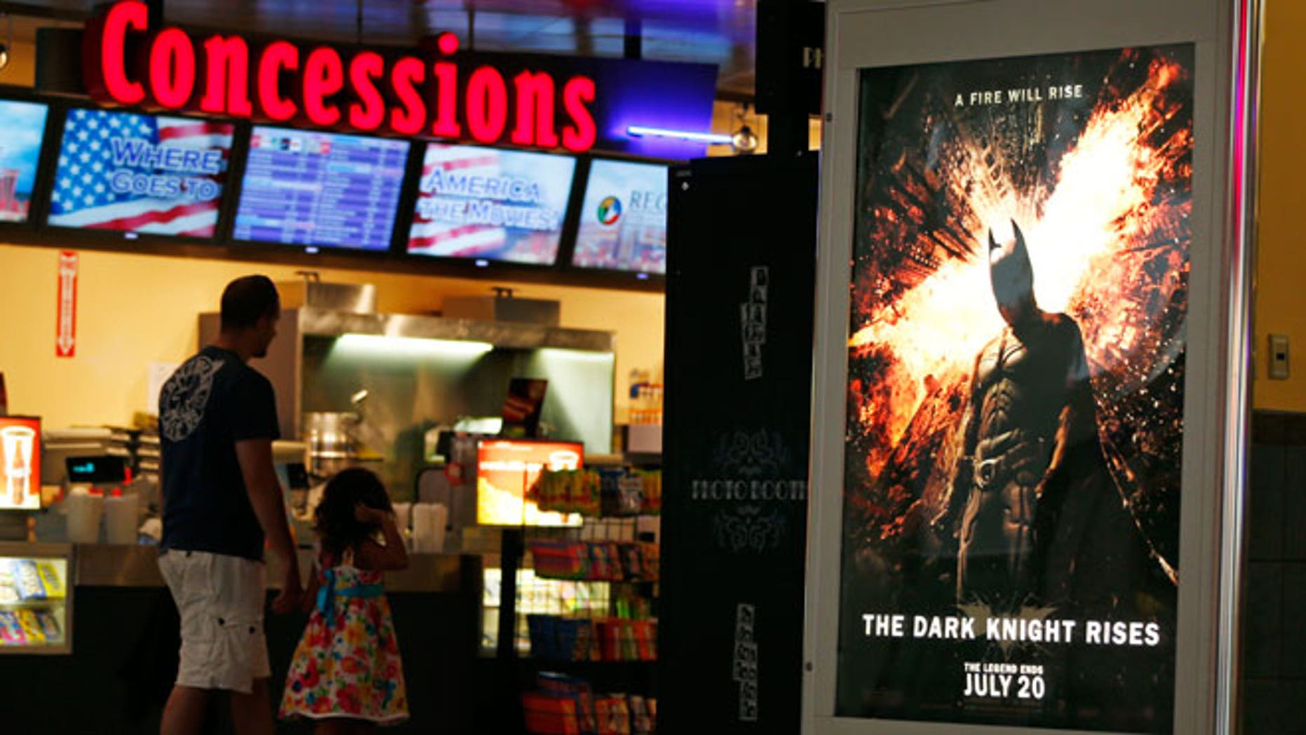 "FILE - In this July 20, 2012 file photo, people walk past a ""The Dark Knight Rises,"" at Regal Cinemas at Crossgates Mall in Albany, N.Y."