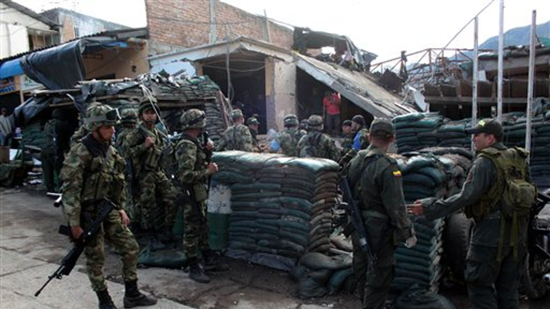 Police officers and soldiers stand in front of the destroyed police station of Inza, in Colombia's southern Cauca state, Saturday, Dec. 7, 2013. The Colombian Army said that five members of the military, two civilians and a police officer were killed after rebels of the Revolutionary Armed Forces of Colombia, FARC, threw artisanal mortar at the post from a truck, destroying that and several other buildings. (AP Photo/Juan Bautista Diaz)
