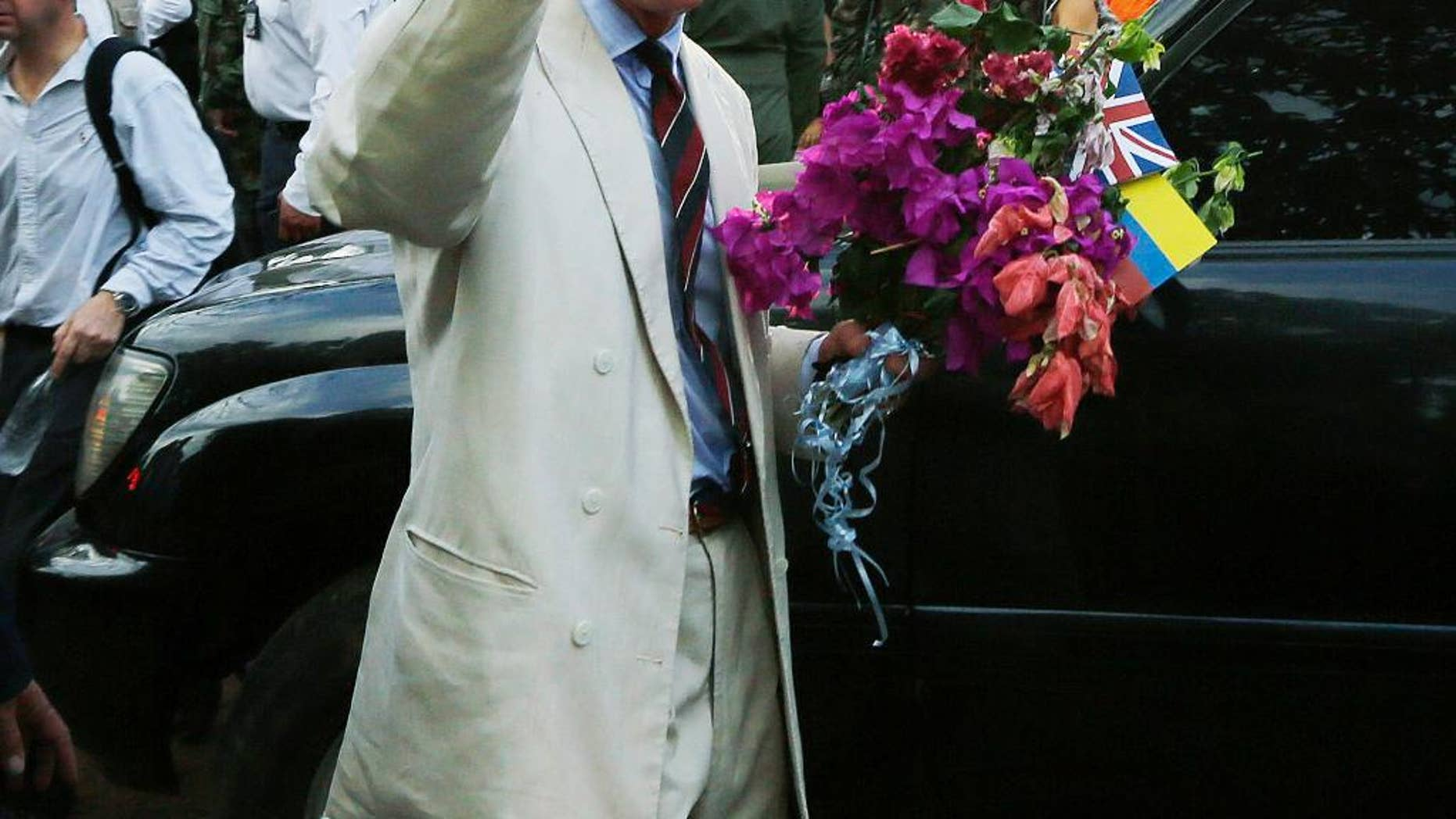 Britain's Prince Charles, right, waves towards local residents as he holds a bouquet of flowers that was given to him during a visit to La Macarena, Colombia, Thursday, Oct. 30, 2014. Prince Charles and his wife Camilla are in Colombia as part of a nine-day tour of Latin America. (AP Photo/Fernando Vergara)