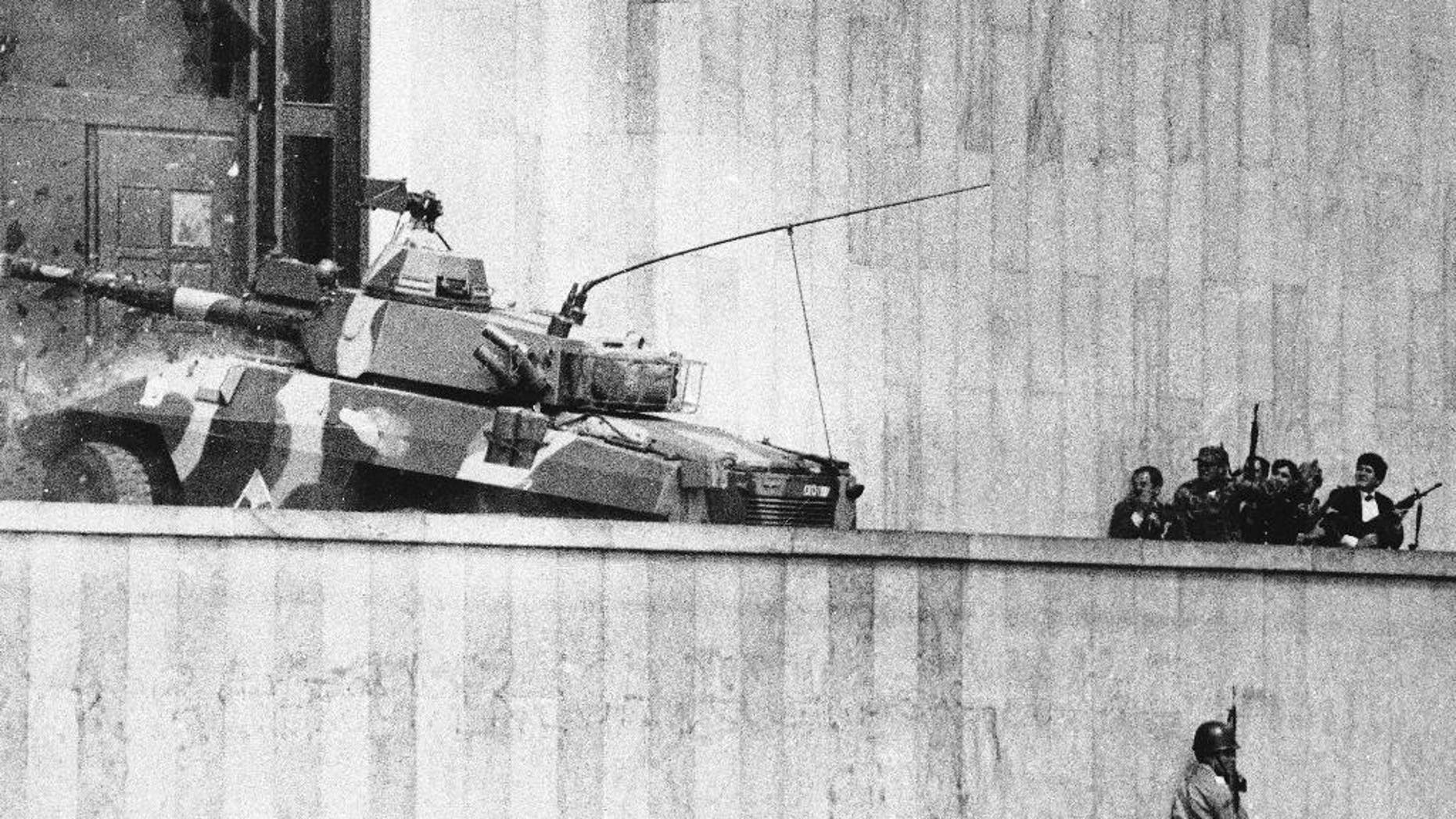 FILE - In this Nov. 6, 1985, file photo, an armored vehicle crashes through the two story wooden doors at the front entrance to the Palace of Justice in Bogota, as soldiers and policemen prepared to rush inside. The Inter-American Court of Human Rights has charged Colombia, Wednesday Dec. 10, 2014, with human rights violations in connection with the disappearance of 10 people in 1985's hostage crisis at the Supreme Court. The court ordered Colombia to provide relatives with compensation and psychological assistance, publish its sentence in national news media, and continue investigating the case. In addition to those disappeared, more than 100 people were killed in the government operation to retake the building, including all rebels and many judges. (AP Photo/Carlos Gonzalez, File)