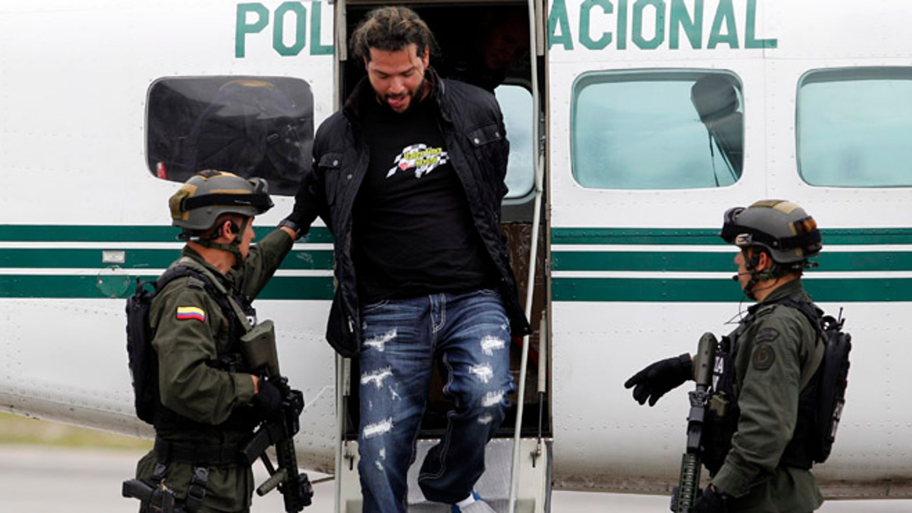 """Aug. 8, 2012: Police escort from a plane alleged drug trafficker Erickson Vargas Cardona, alias """"Sebastian,"""" described as the boss of the """"Office of Envigado,"""" as he walks down the stairs in handcuffs at a police station inside the airport in Bogota, Colombia."""
