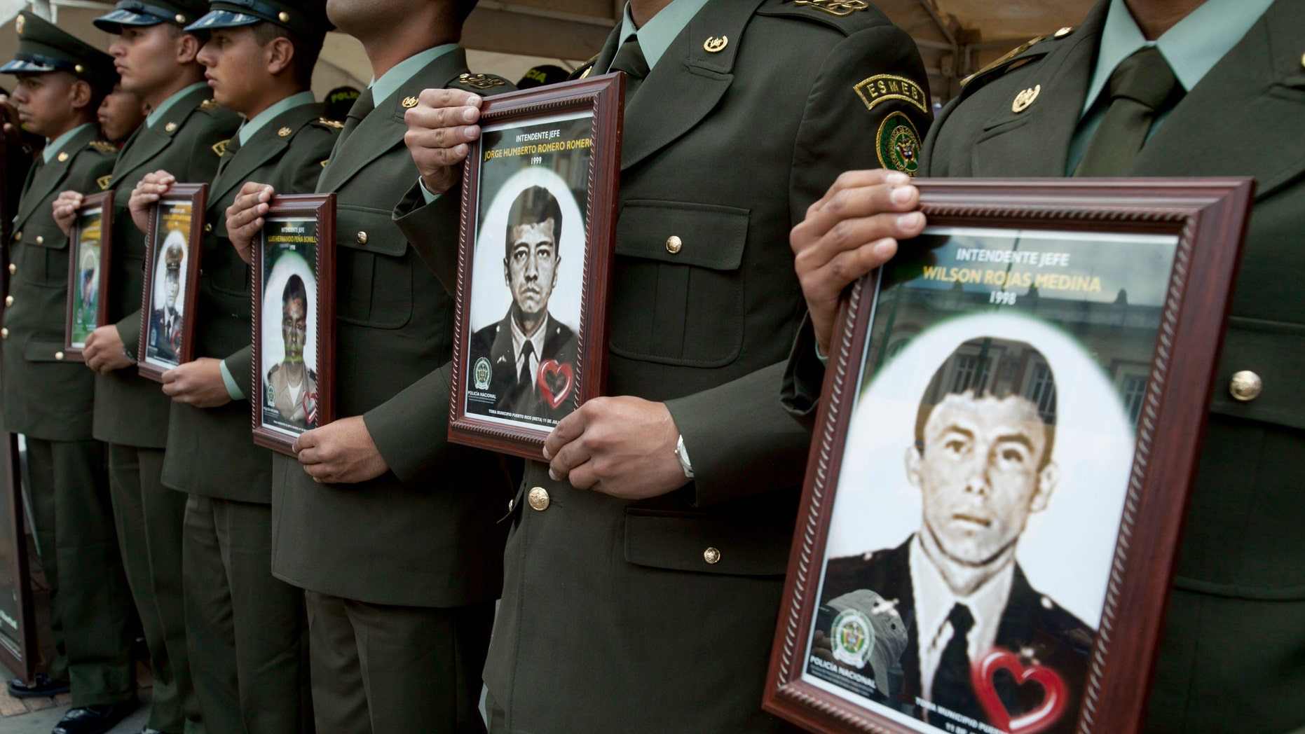 Police officers hold photographs of fellow officers, who were kidnapped by rebels of the Revolutionary Armed Forces of Colombia (FARC), in the main square during a protest to demand his freedom in Bogota, Colombia, Thursday Feb. 23, 2012. (AP Photo/Fernando Vergara)