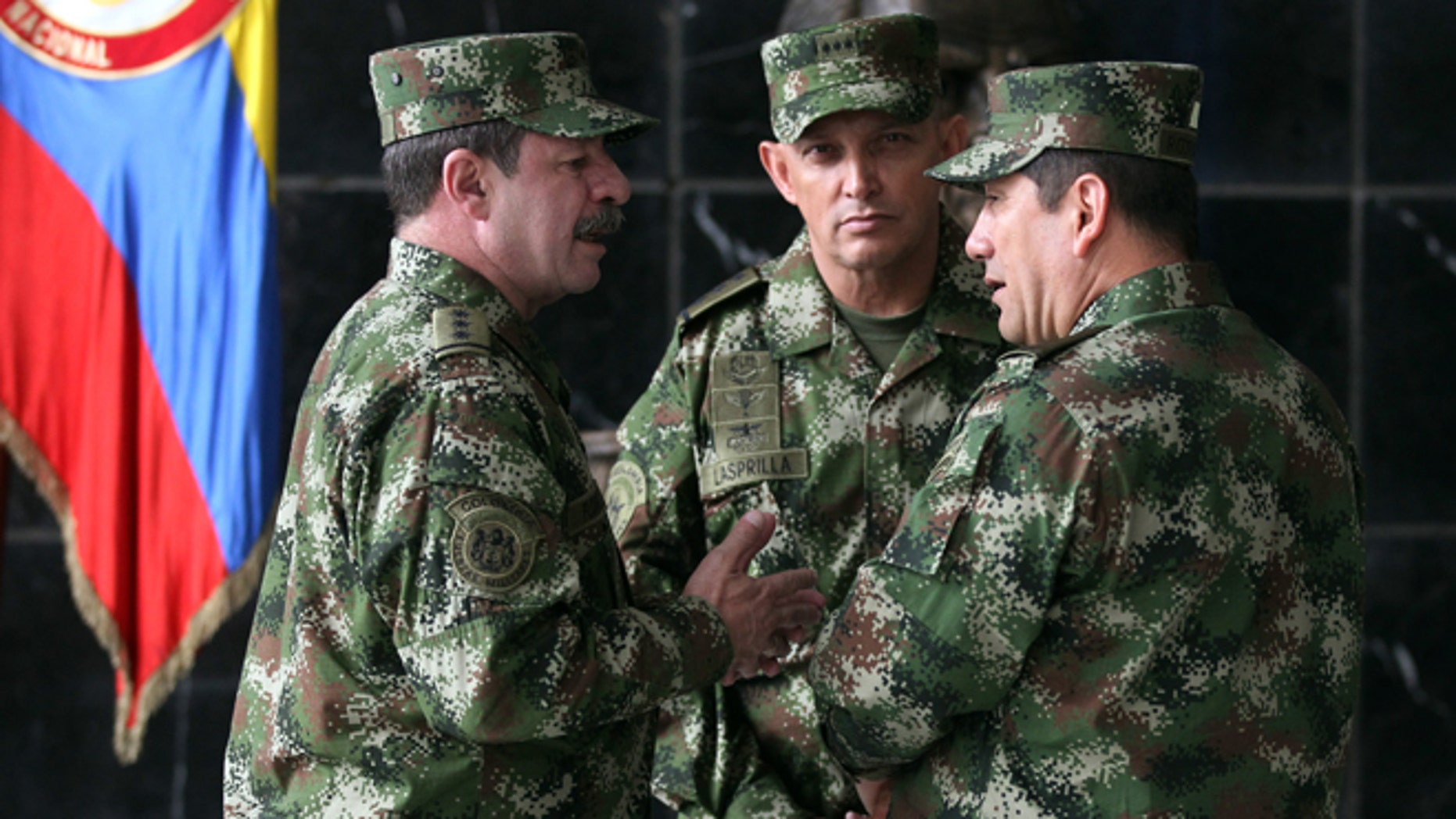 FILE - In this Feb. 18, 2014, file photo, the new Colombian armed forces commander Gen. Juan Pablo Rodríguez, right, talks to newly appointed chief of staff Gen. Javier Florez, left, and army commander Gen. Jaime Lasprilla, center, after a press conference where Defense Minister Juan Carlos Pinzon announced the firing of the fromer armed forces chief Gen. Leonardo Barrero in Bogotá, Colombia. Gen. Rodríguez and Gen. Lasprilla are among dozens of senior Colombian army officers implicated in the killing of 3,000 civilians falsely claimed to be rebels a decade ago have risen through the ranks and are escaping punishment for their roles in one of the worst atrocities committed in Latin America, Human Rights Watch said Wednesday, June 23, 2015. (AP Photo/Fernando Vergara, File)