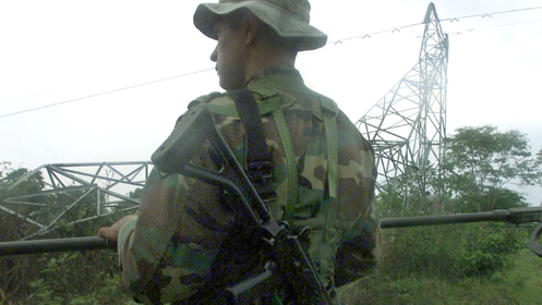 403962 01: A Colombian soldier searches for possible land mines left by the FARC, The Revolutionary Armed Forces of Colombia, after the group dynamited an energy tower owned by the state operated national energy distribution network, ISA, April 15, 2002 in Saravena, Colombia. The companys energy towers have been attacked repeatedly this year by the guerrilla group in a war against state-owned infrastructure leaving entire states without energy, sometimes for weeks. (Photo by Carlos Villalon/Getty Images)