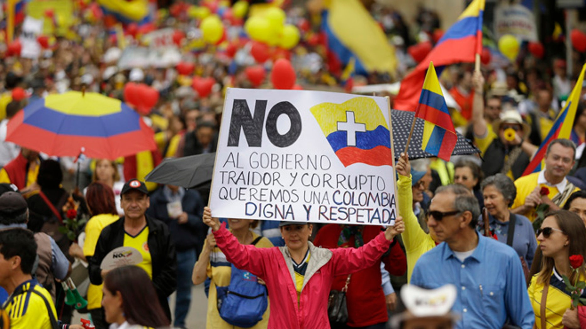 """Colombians march to protest against President Juan Manuel Santos' government and denounce the concessions the government has made in peace talks with the Revolutionary Armed Forces of Colombia, or FARC,  in Bogota, Colombia, Saturday, April 2, 2016.  The message on the poster at center reads in Spanish; """"No more to a traitorous and corrupt government. We want a dignified and respected Colombia."""" (AP Photo/Fernando Vergara)"""
