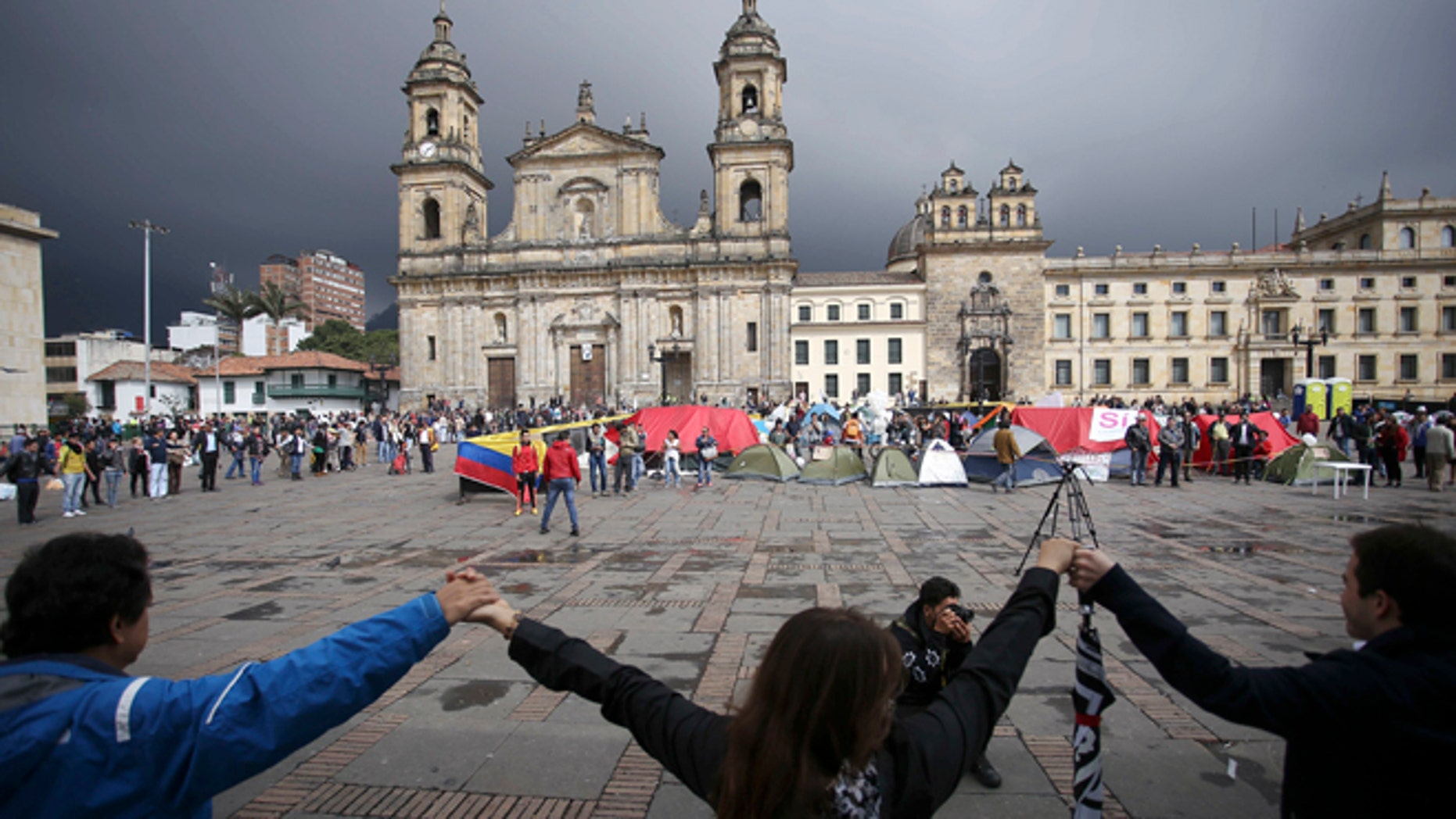 Demonstrators hold hands to support a peace accord between the Colombian government and rebels of the Revolutionary Armed Forces of Colombia, FARC, at the main square in Bogotá, Colombia, Saturday, Oct. 8, 2016. Dozens of people are camping at the Bolívar square in support of the peace process. Voters narrowly rejected in a referendum a peace accord signed between President Juan Manuel Santos and the FARC. (AP Photo/Ivan Valencia)