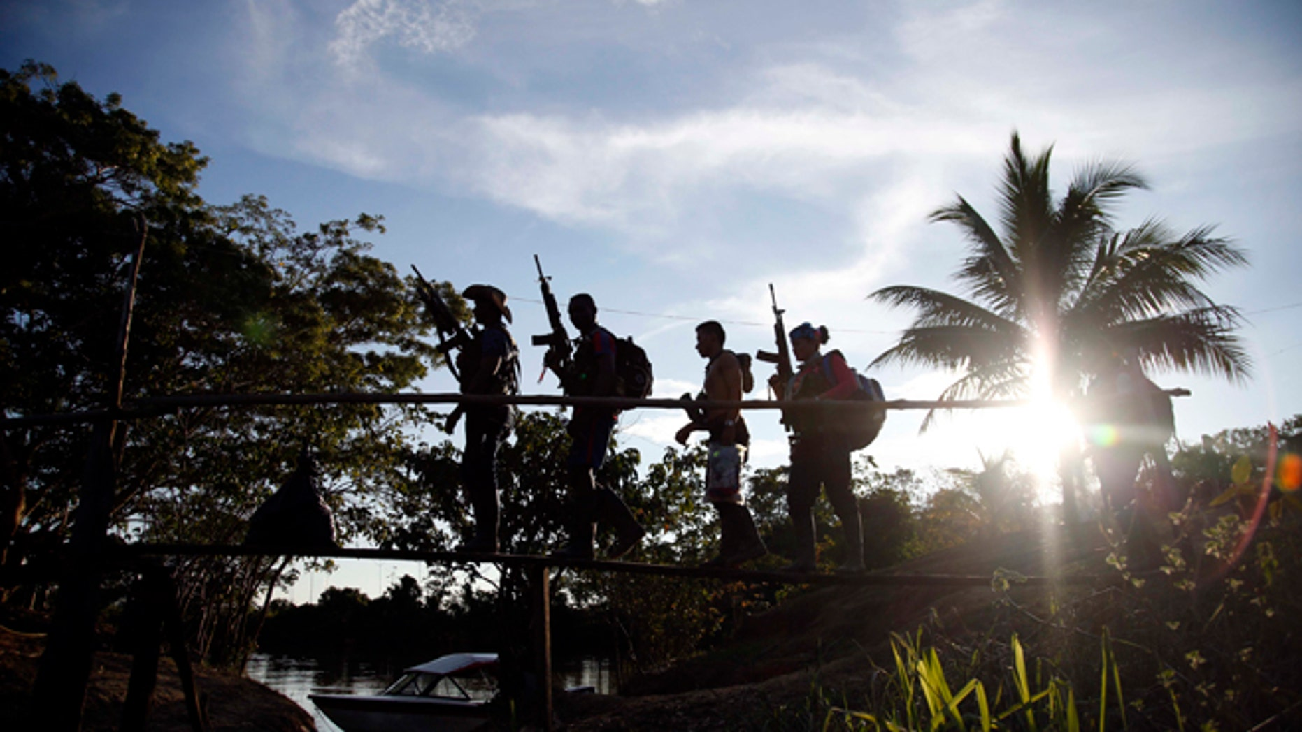 In this Aug. 12, 2016 photo, rebels of the 48th Front of the Revolutionary Armed Forces of Colombia walk on a makeshift footbridge in the southern jungles of Putumayo, Colombia. (AP Photo/Fernando Vergara)