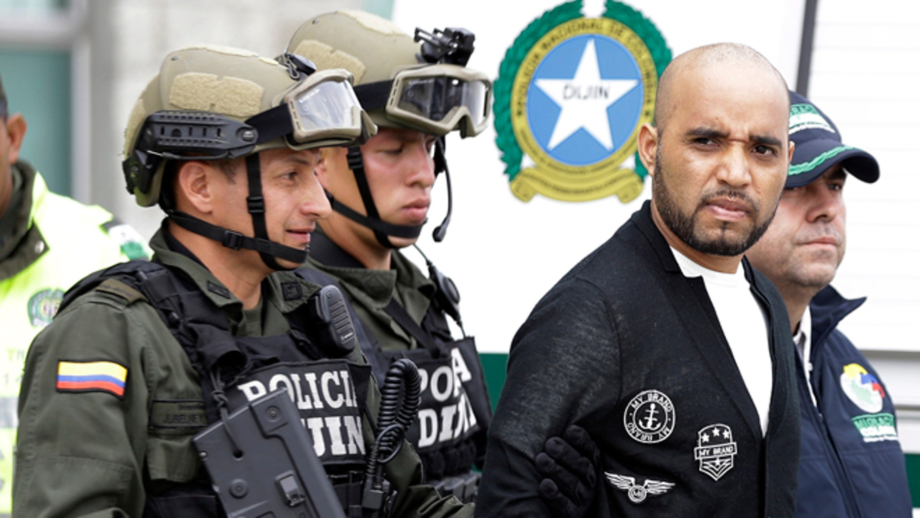 Alleged Peruvian drug trafficker Gerson Galvez, right, is escorted by police officers to a waiting Peruvian Air Force plane, in Bogota, Colombia, Sunday, May 1, 2016. Galvez who is one of Peru's most wanted criminals was captured by the Colombian police in Medellín on Saturday and was handed over to the Peruvian authorities. (AP Photo/Fernando Vergara)