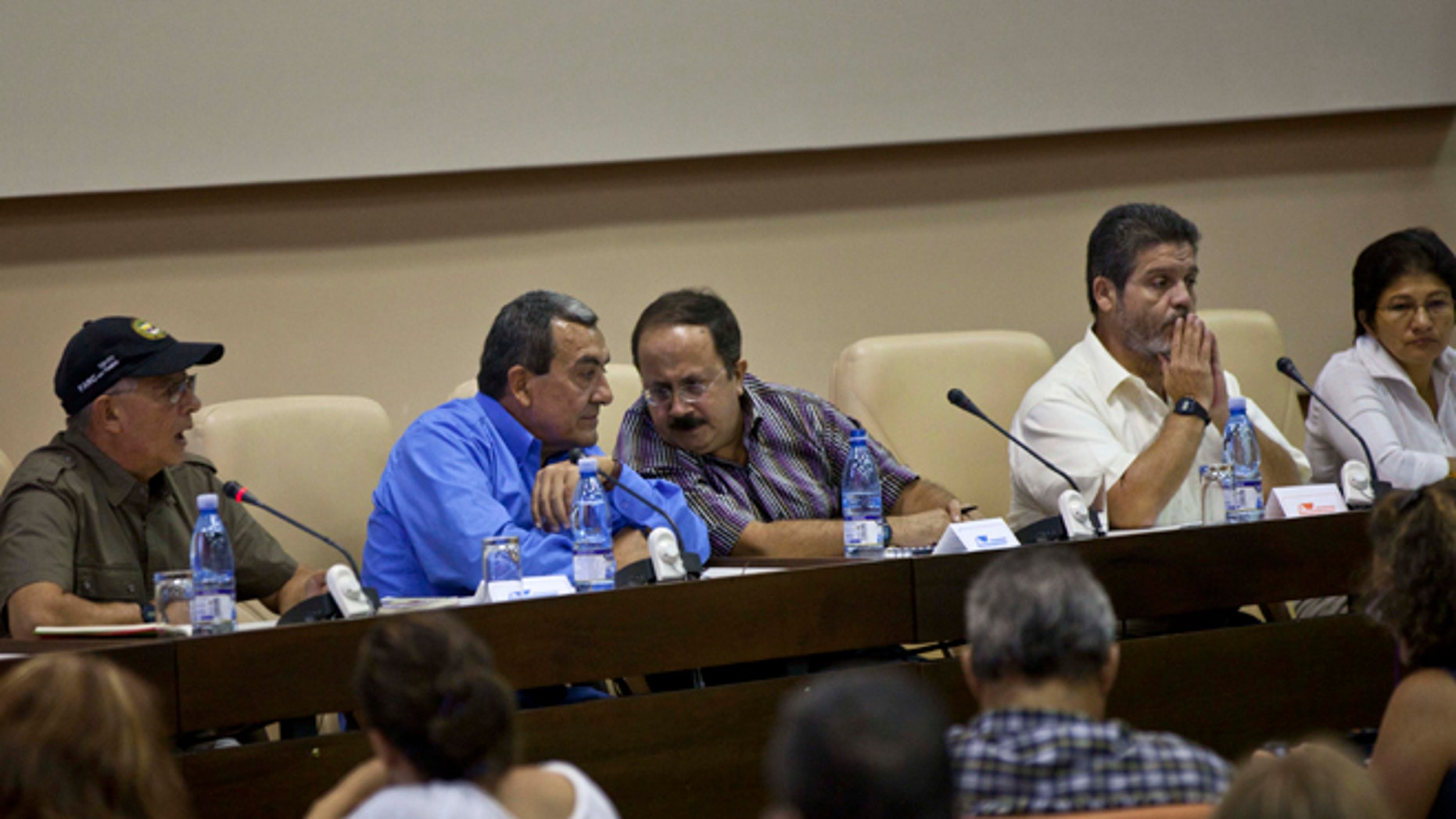 Mauricio Jaramillo, a spokesman and top leader of the Revolutionary Armed Forces of Colombia, or FARC, second from left, talks with FARC member Andres Paris during a press conference in Havana, Cuba, Thursday, Sept. 6, 2012. Colombia's main leftist rebel group announced two of its negotiators on Thursday for October peace talks in Norway, and said it hopes a high-ranking guerrilla imprisoned in the United States also can take part. (AP Photo/Ramon Espinosa)