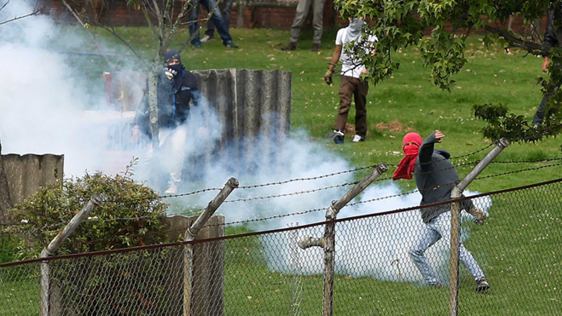 A university students motions to throw back a teargas canister at riot police during a protest in support of a national strike in Bogota, Colombia, Tuesday, Aug. 20, 2013. Truckers, coffee workers and health workers joined agricultural and mining workers in one of the largest national strikes ever faced by the Colombian government. The strikers demands include reduced gas prices and increased subsidies. (AP Photo/Fernando Vergara)