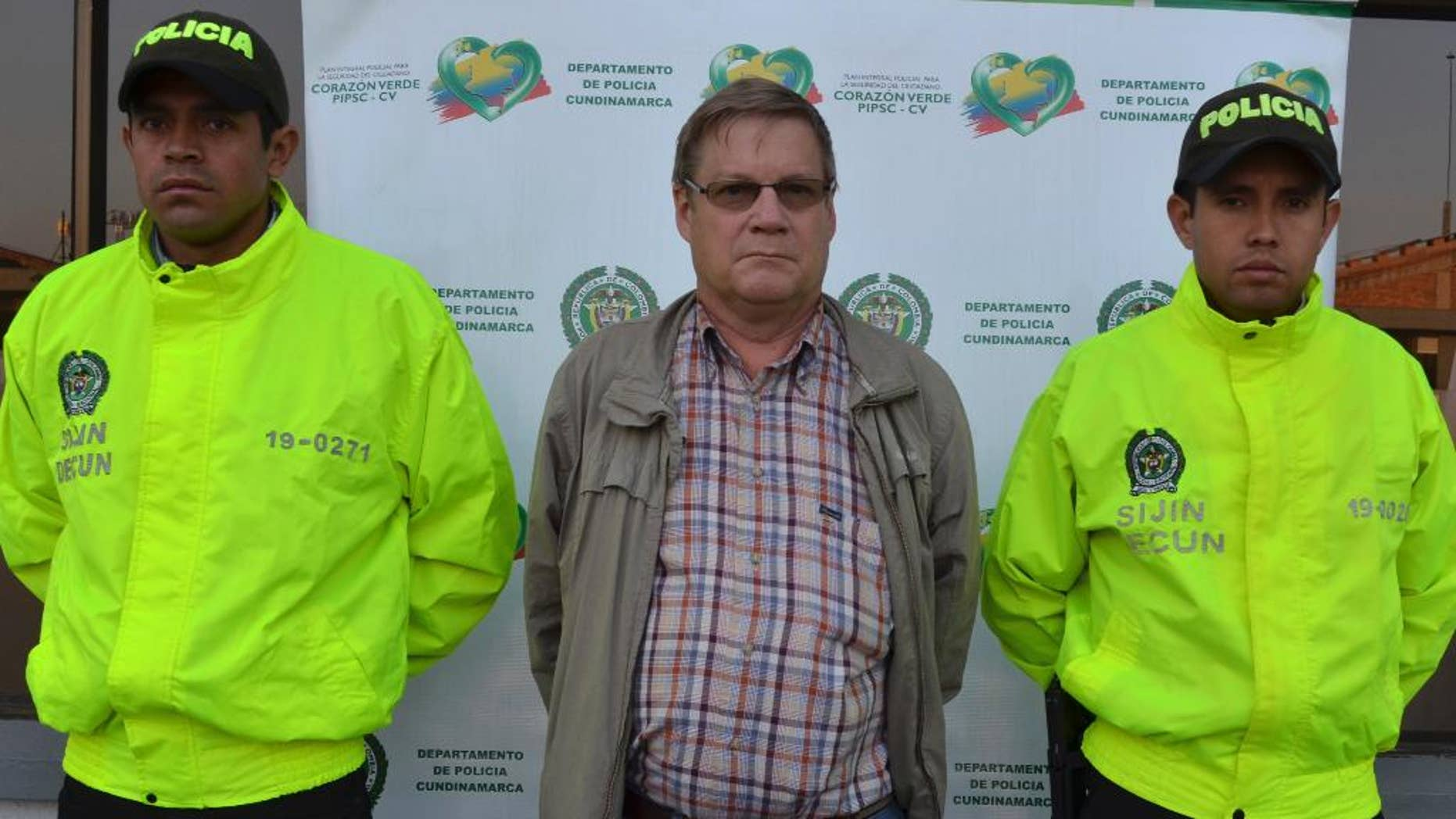 This photo released by Colombia's National Police shows American citizen Martin Stendal flanked by police officers at a police station in Bogota, Colombia, Thursday, Feb. 19, 2015. Police Col. Flavio Meza said that Stendal, a 59-year old native of Minnesota, surrendered Wednesday night to face an arrest warrant charging him with supporting terrorism and collaborating with the Revolutionary Armed Forces of Colombia rebel movement. Stendal says in a video posted online that he had been set up and that his trips into rebel territory to distribute Bibles and radios were only for ministering. (AP Photo/Colombia's National Police)