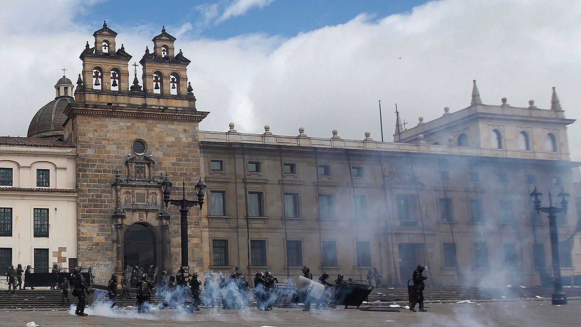 Riot police stand in the capital's main square during clashing with students in downtown Bogota, Colombia, Thursday, Aug. 29, 2013.