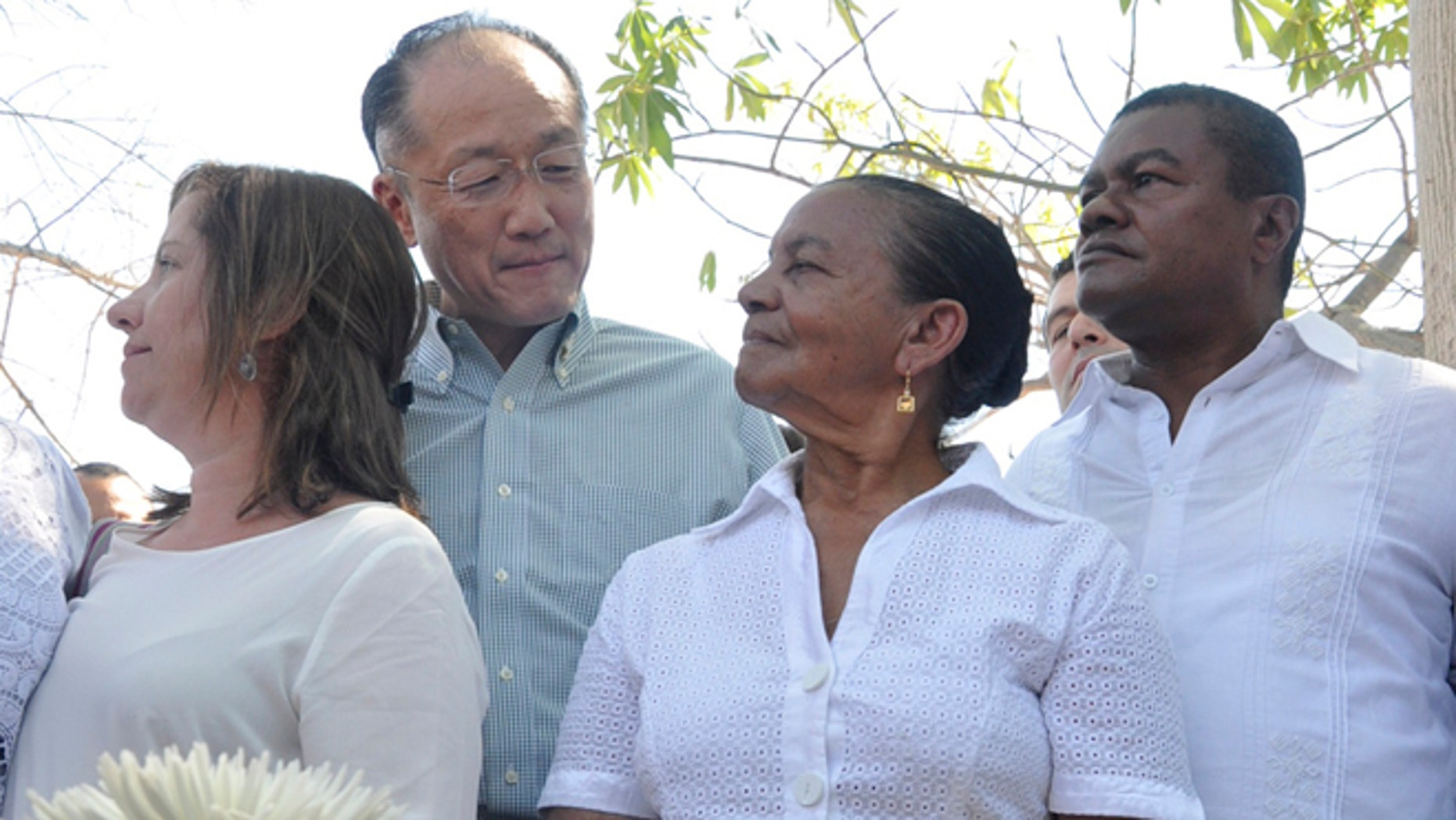 World Bank President Dr. Jim Yong Kim looks at Norma Quiroz, widow of slain community activist Aljemiro Quiroz, in Guacoche, Colombia, Thursday, Jan. 14, 2016.