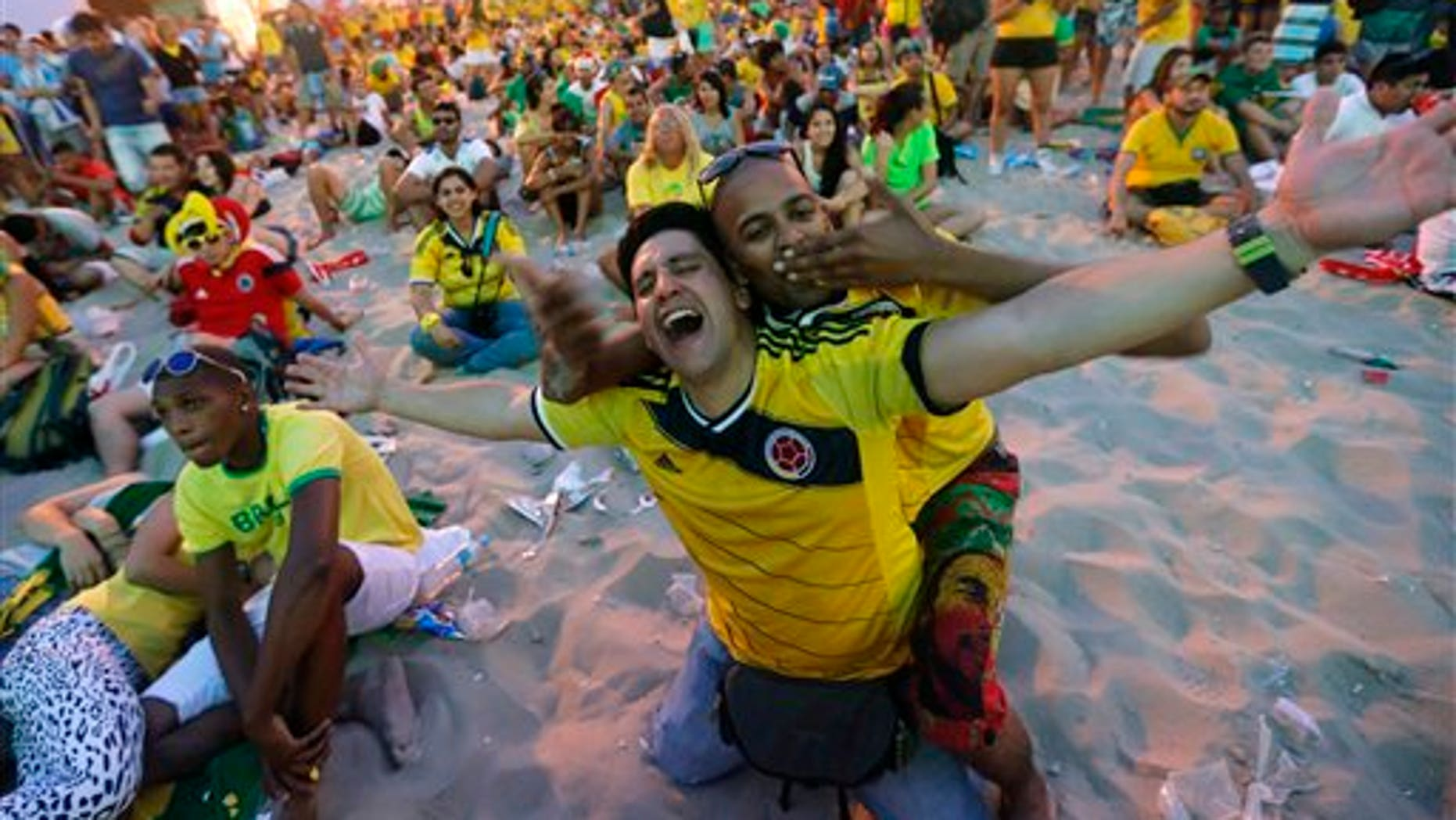 FILE - In this June 28, 2014, file photo, Colombia soccer fans celebrate a goal against Uruguay as they watch the World Cup round of 16 match inside the FIFA Fan Fest area on Copacabana beach in Rio de Janeiro, Brazil.