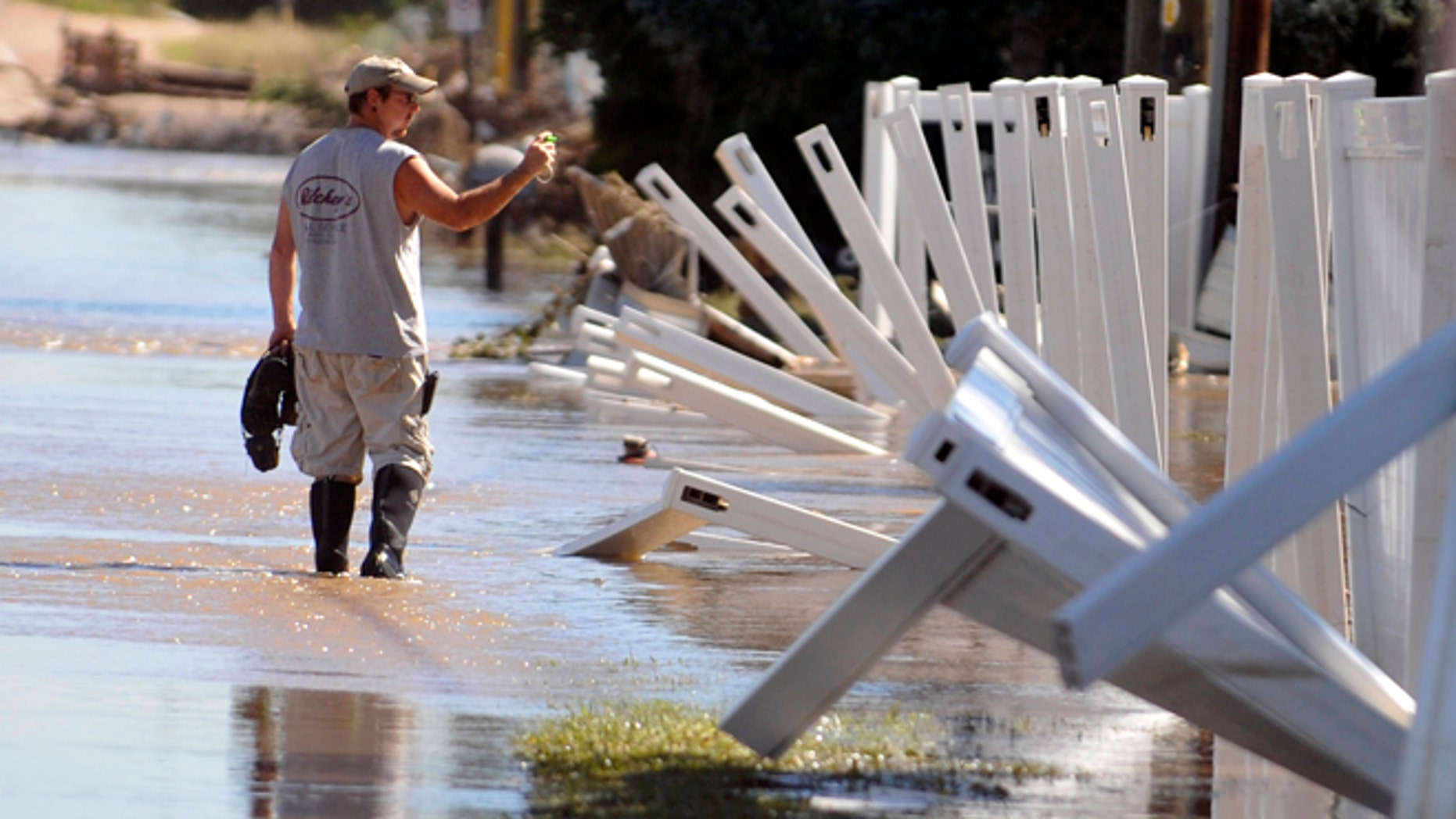 A man wades through the flood waters Sept. 18, 2013 in Evans, Colo. Residents are advised to wash everything that comes in contact with the water. (AP Photo/The Greeley Tribune, Joshua Polson)