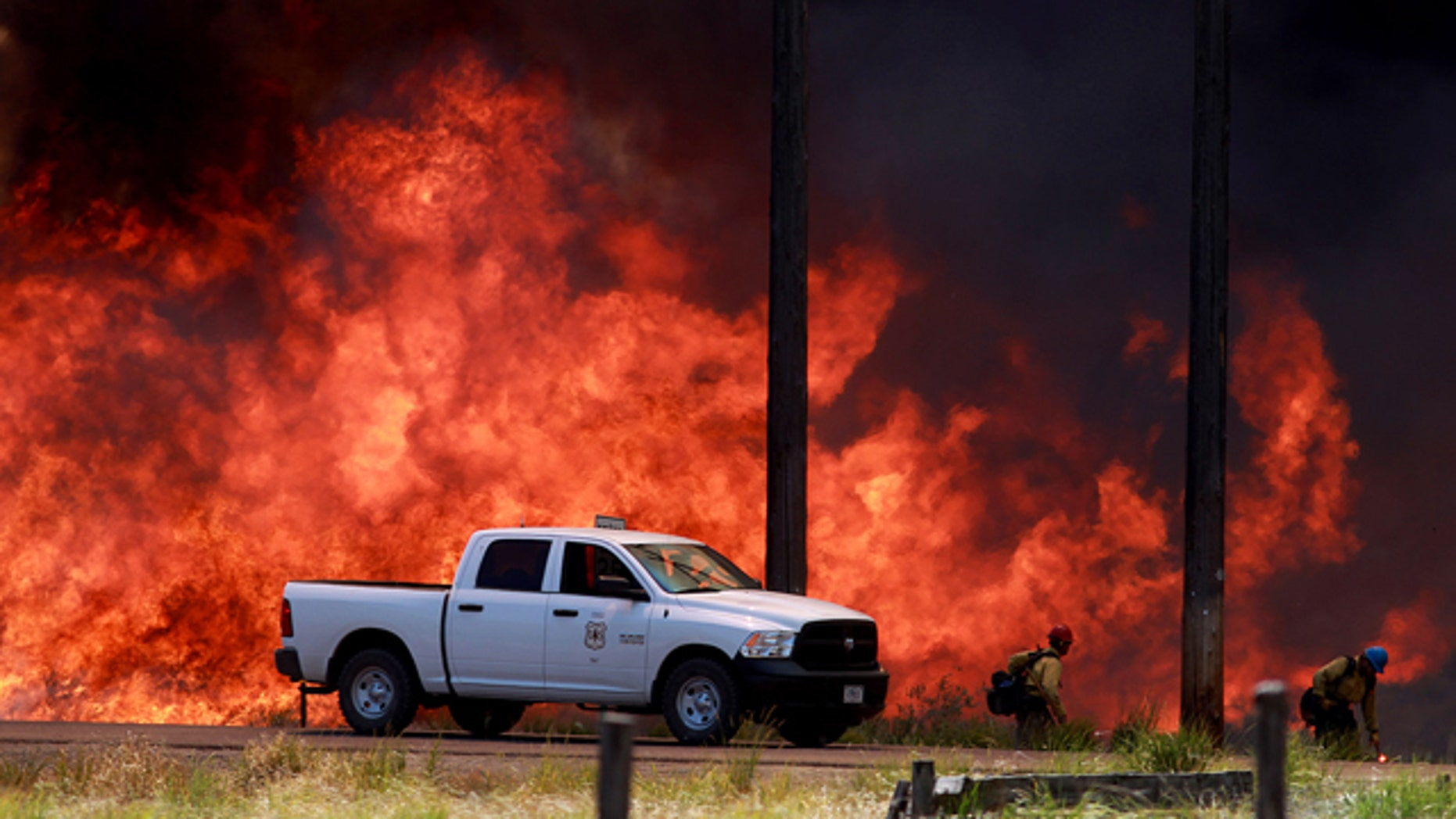 July 7, 2014: Firefighters with the Bureau of Land Managment battle the Colorado Gulch fire as it advances towards homes near Hailey, Idaho. (AP Photo/Times-News, Ashey Smith)