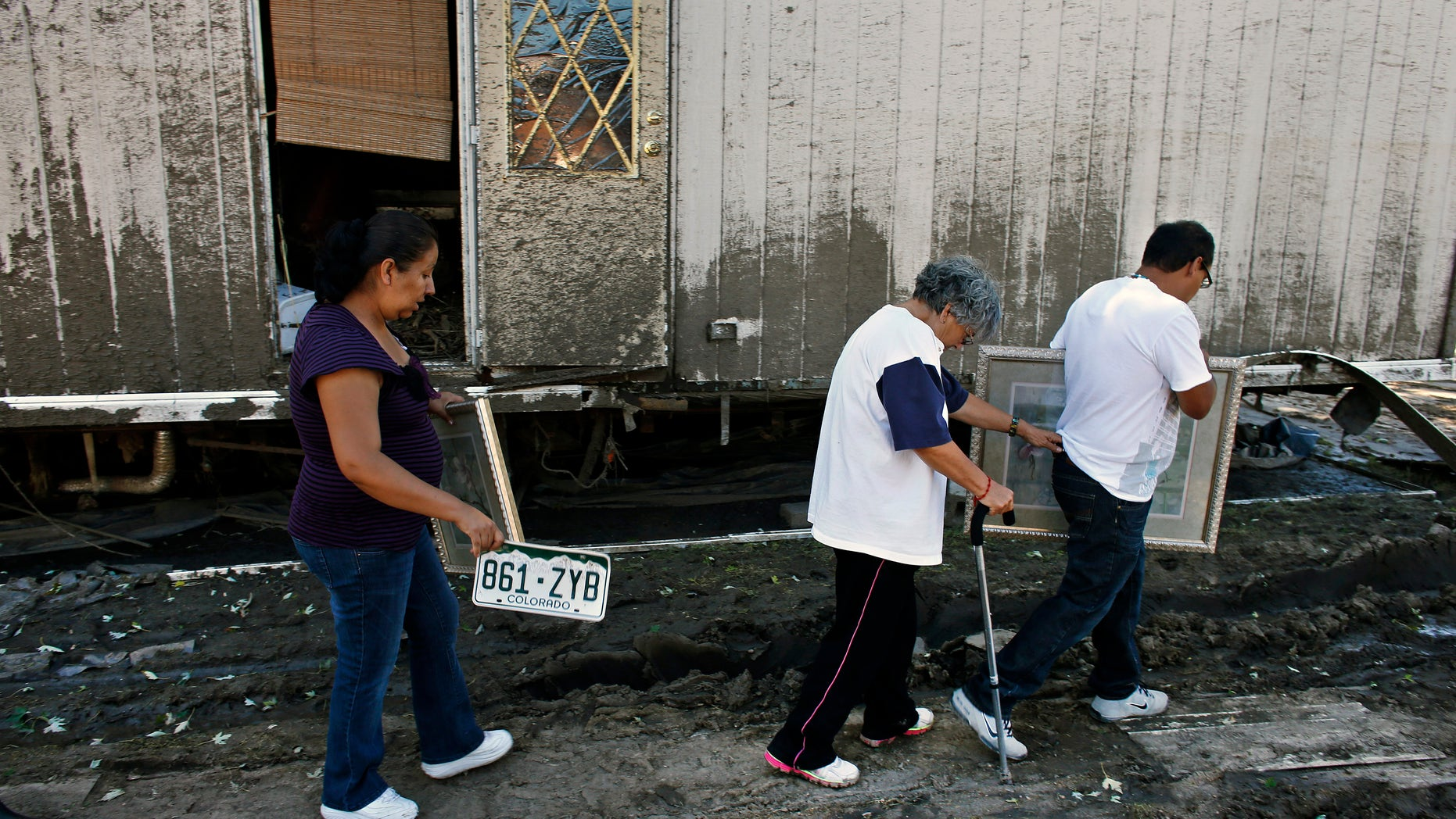 In this Sept. 24, 2013, photo, resident Mari Partida, left, walks with the plate from her destroyed car, as her neighbor Sofia Mendez leans on her son for support as he carries a painting recovered from their trailer, one of the many homes now declared uninhabitable due to permanent flood damage at a trailer park in Evans, Colo. Many undocumented immigrants working in the U.S. have returned to their mobile home parks in flood-ravaged Colorado to find that there was little left to salvage. Like many in the stricken region, they didnt have flood insurance. And because many are not citizens or legal residents, they cant get government help. (AP Photo/Brennan Linsley)